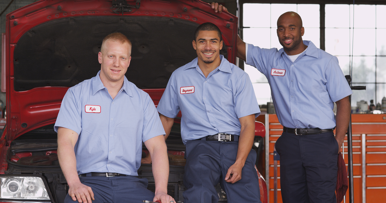 Three auto mechanics in their shop.