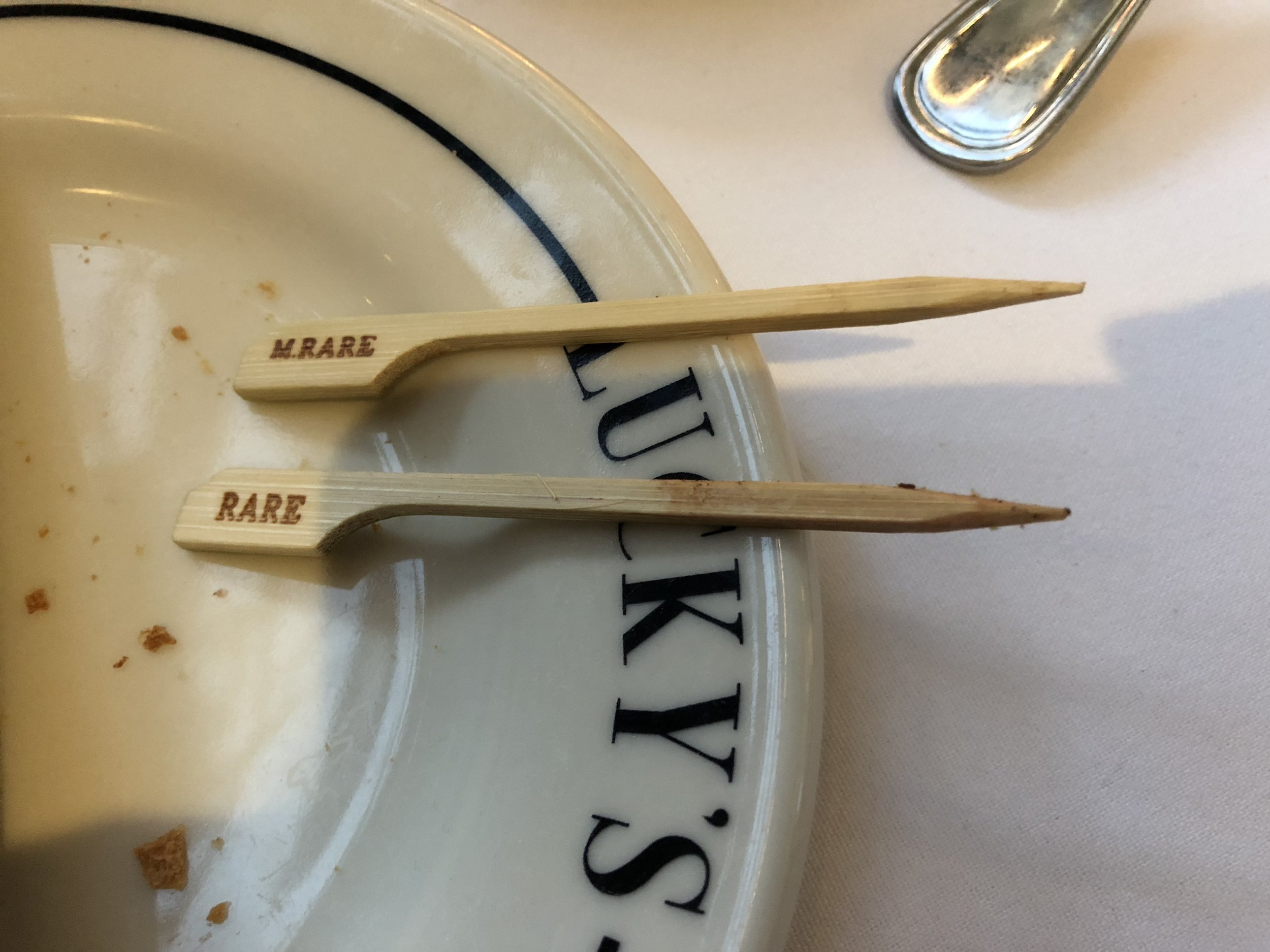 "Two small wooden flags rest on a plate, one says ""M.Rare"" and the other reads ""Rare."""