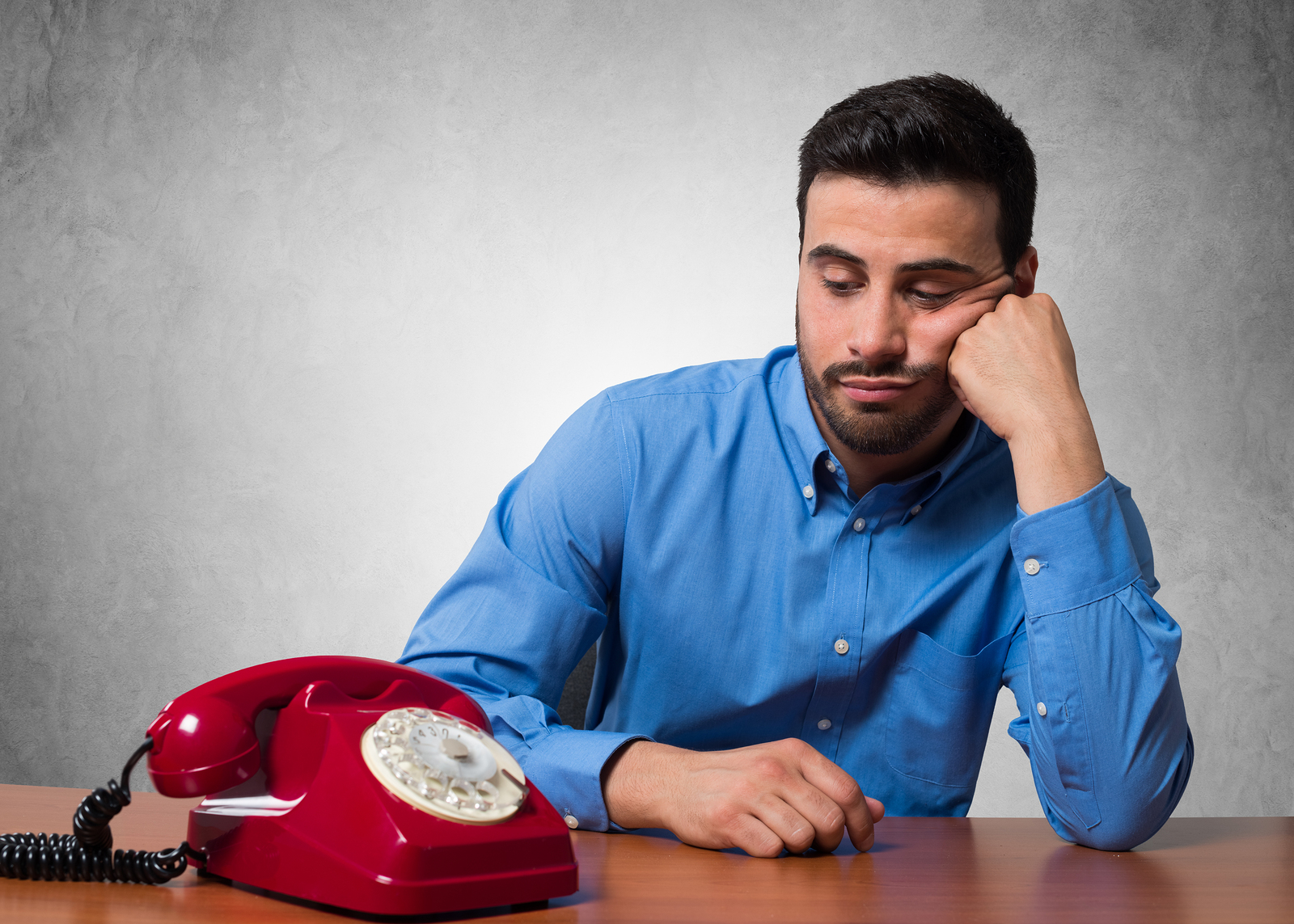 Man waiting for a call to come through on an old, red, rotary phone.
