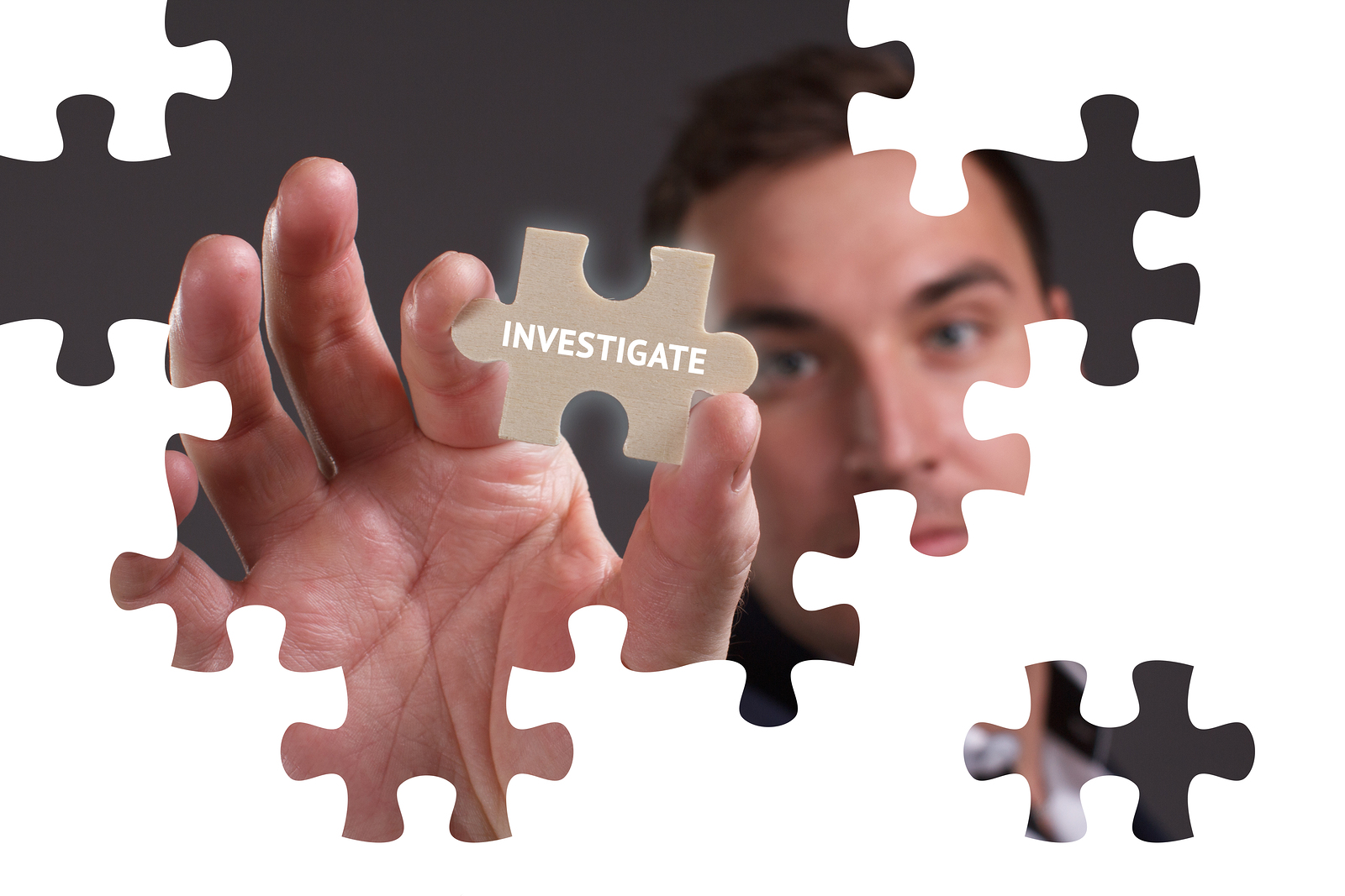 "Man placing a puzzle piece marked ""investigate"" into a puzzle."
