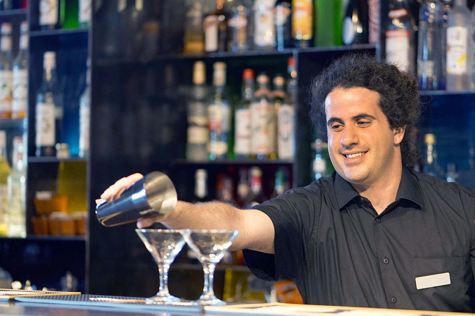 A smiling hotel bartender pouring drinks.