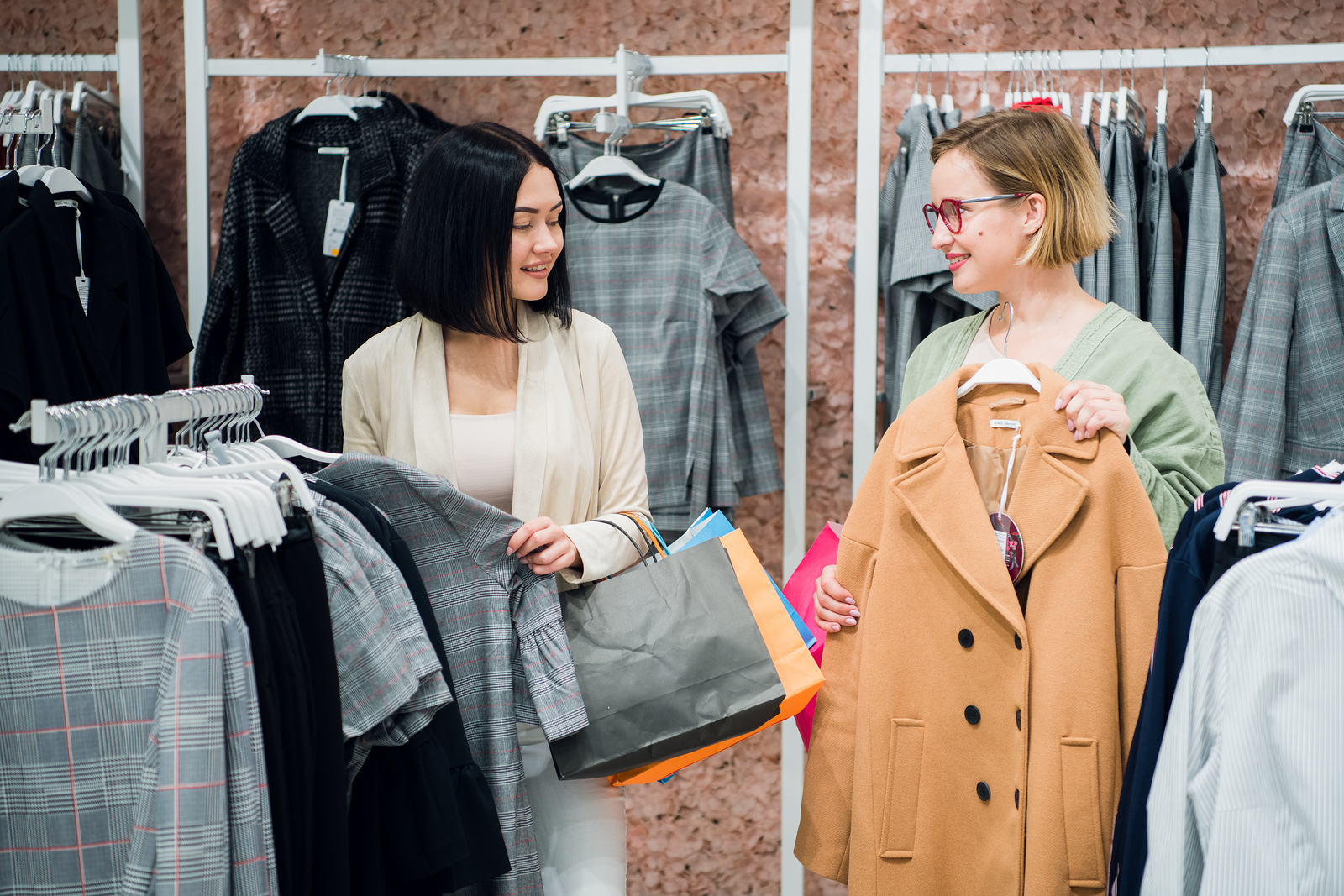 A smiling retail associate helps a customer in a clothing store.