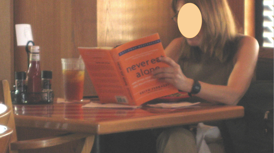 "A woman sits in a restaurant, eating alone while reading a book called ""Never Eat Alone."""