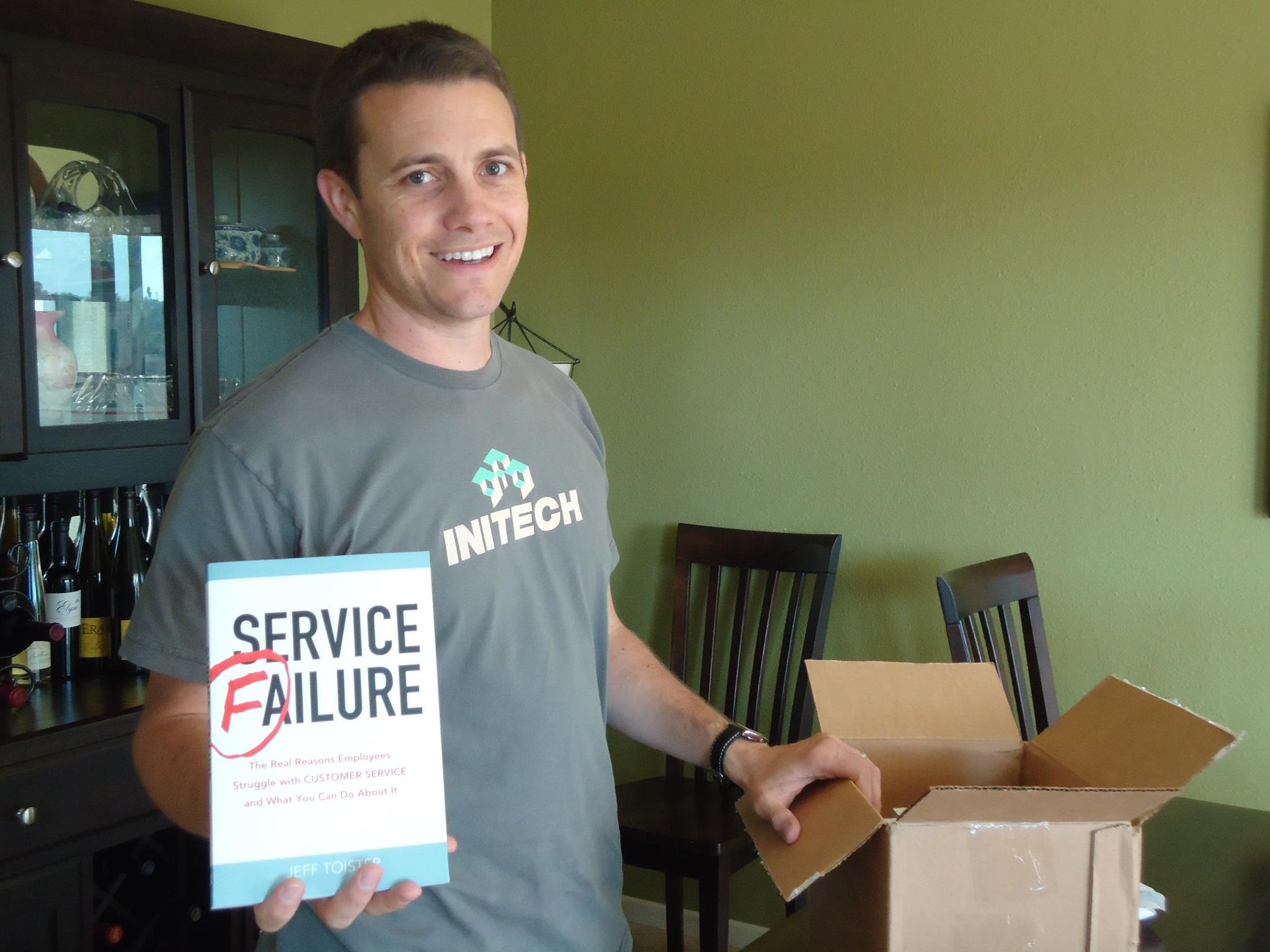 The author, Jeff Toister, holding up his first book,  Service Failure .