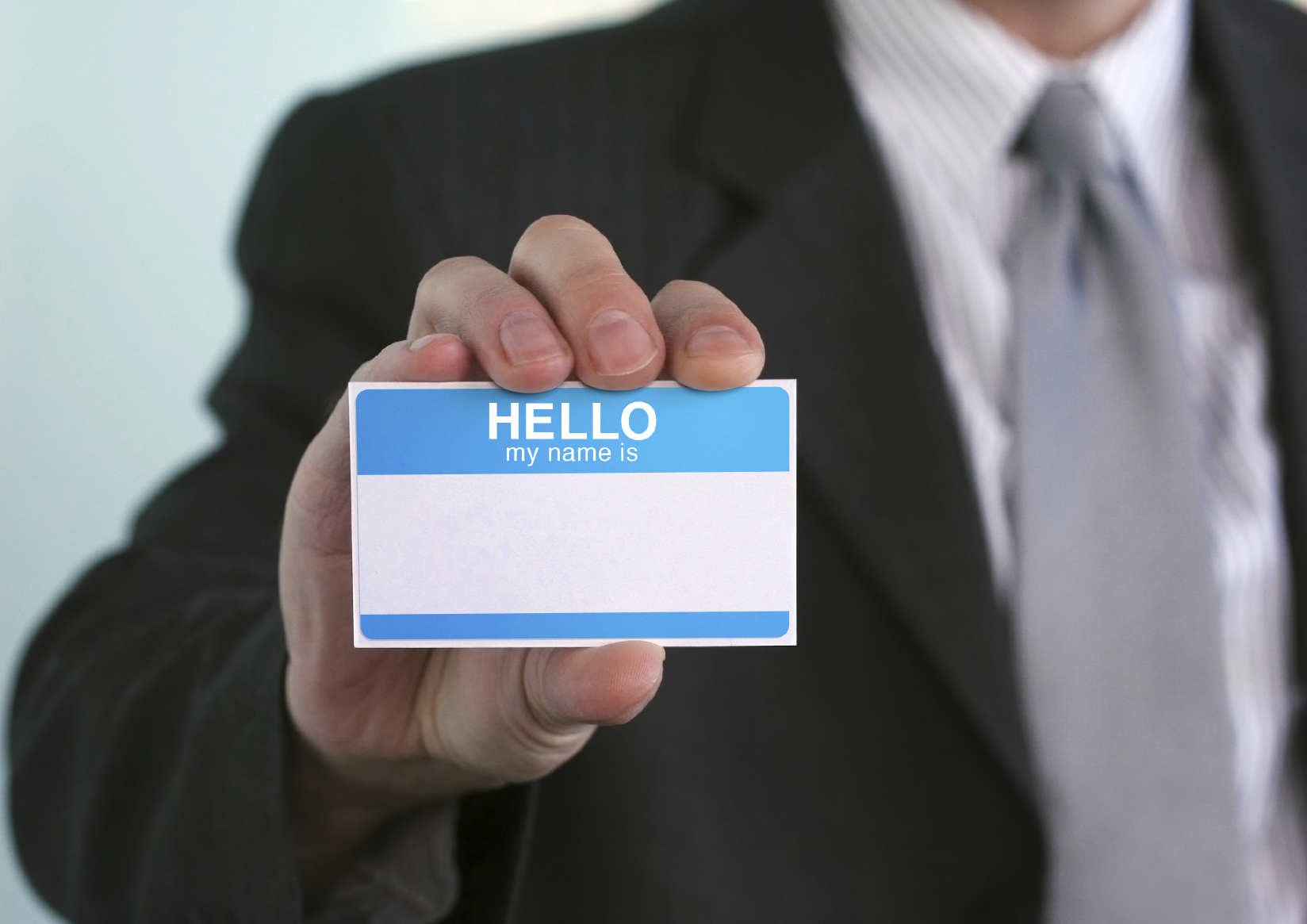 Business person holding up a name tag.