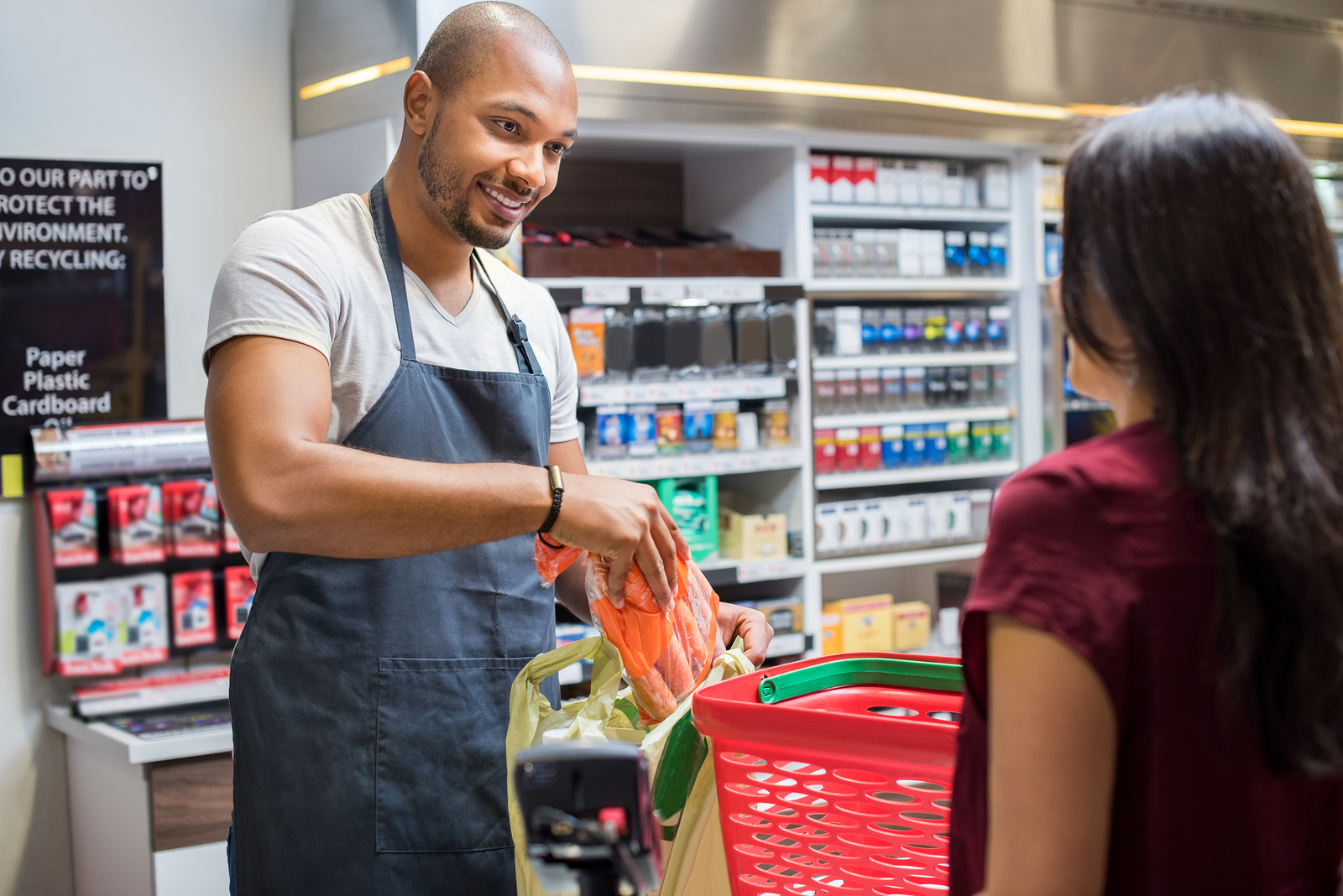 A smiling grocery store cashier bagging groceries for a customer.