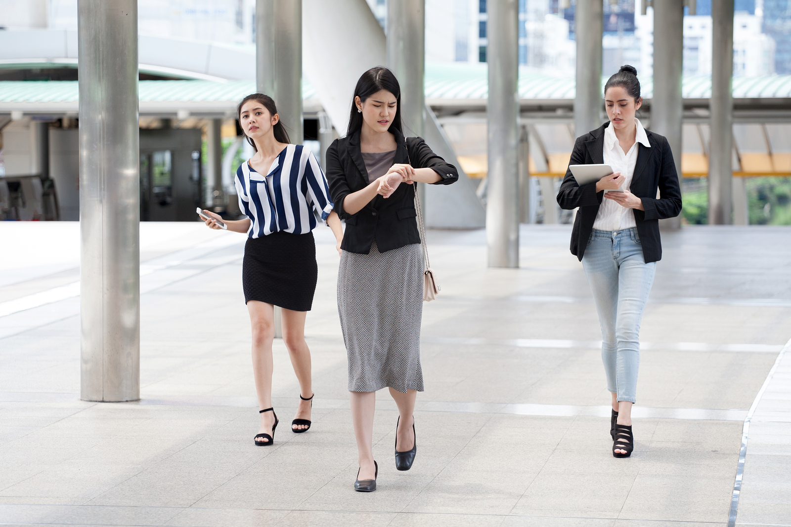 Group of businesswomen running late.