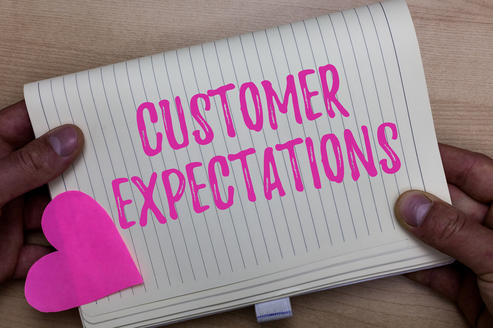 "A person holding a notepad with the words ""customer expectations"" written on it."
