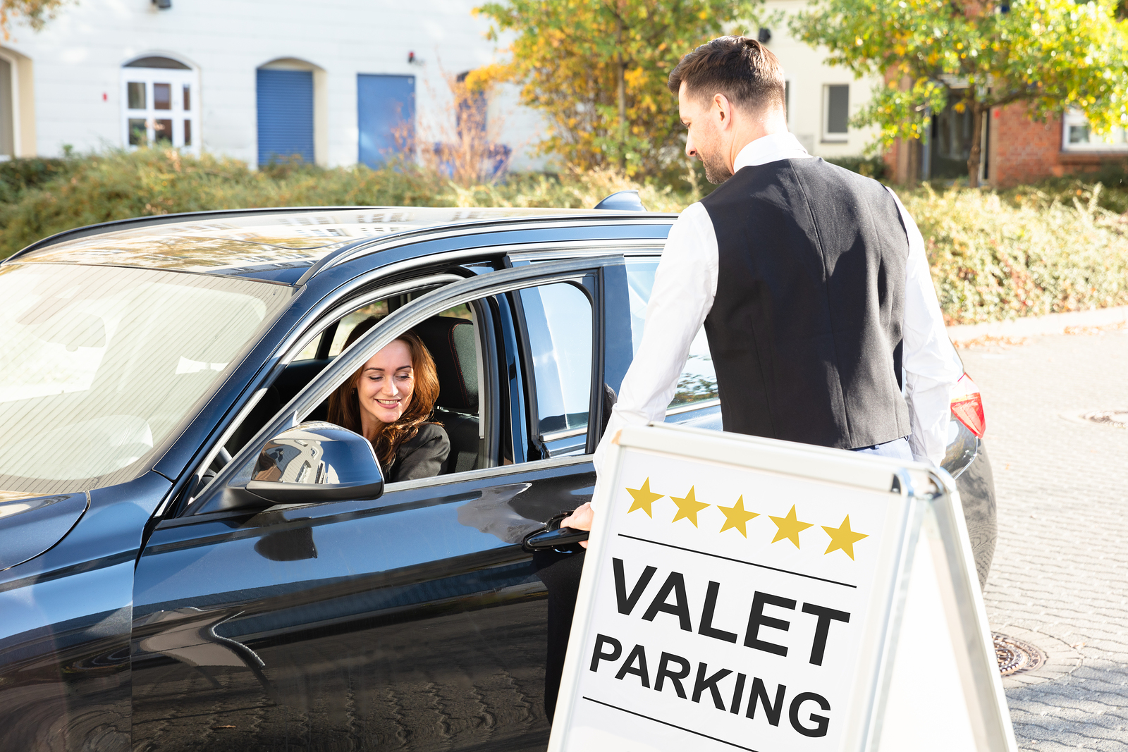A valet parking attendant is opening the car door for a guest.