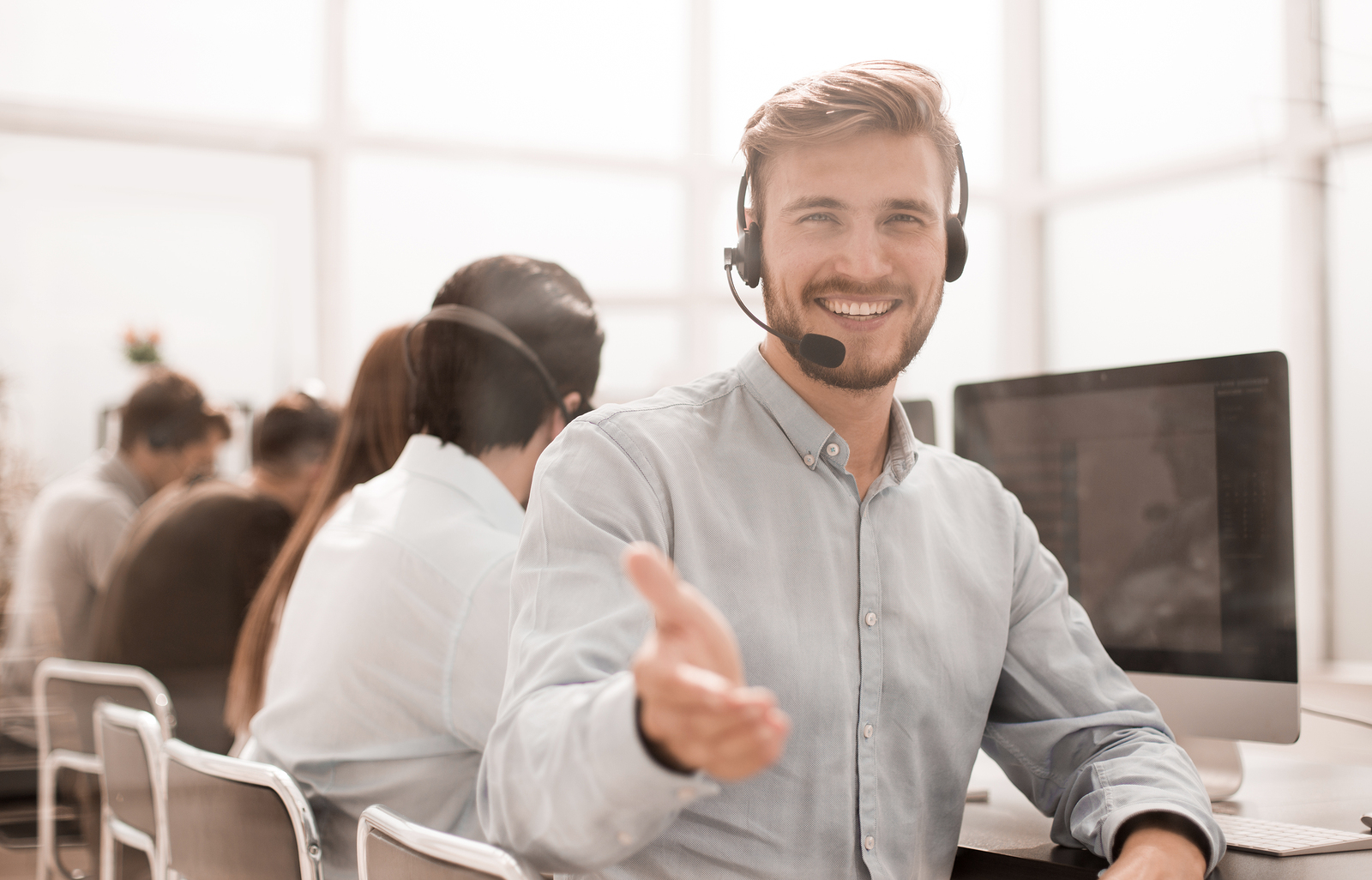 A smiling call center agent greets a customer.