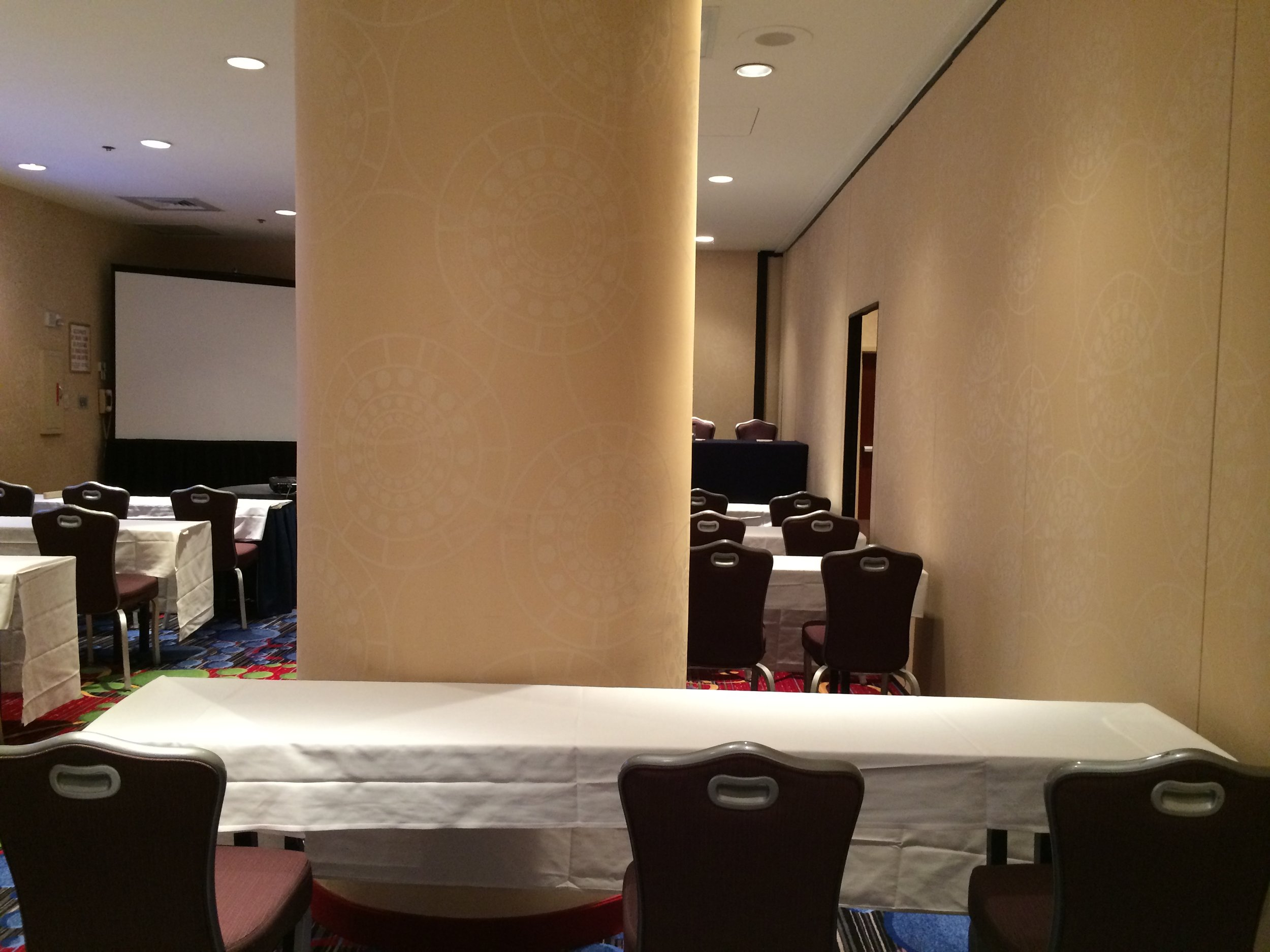 A large pillar blocks the view of participants in a hotel conference room.
