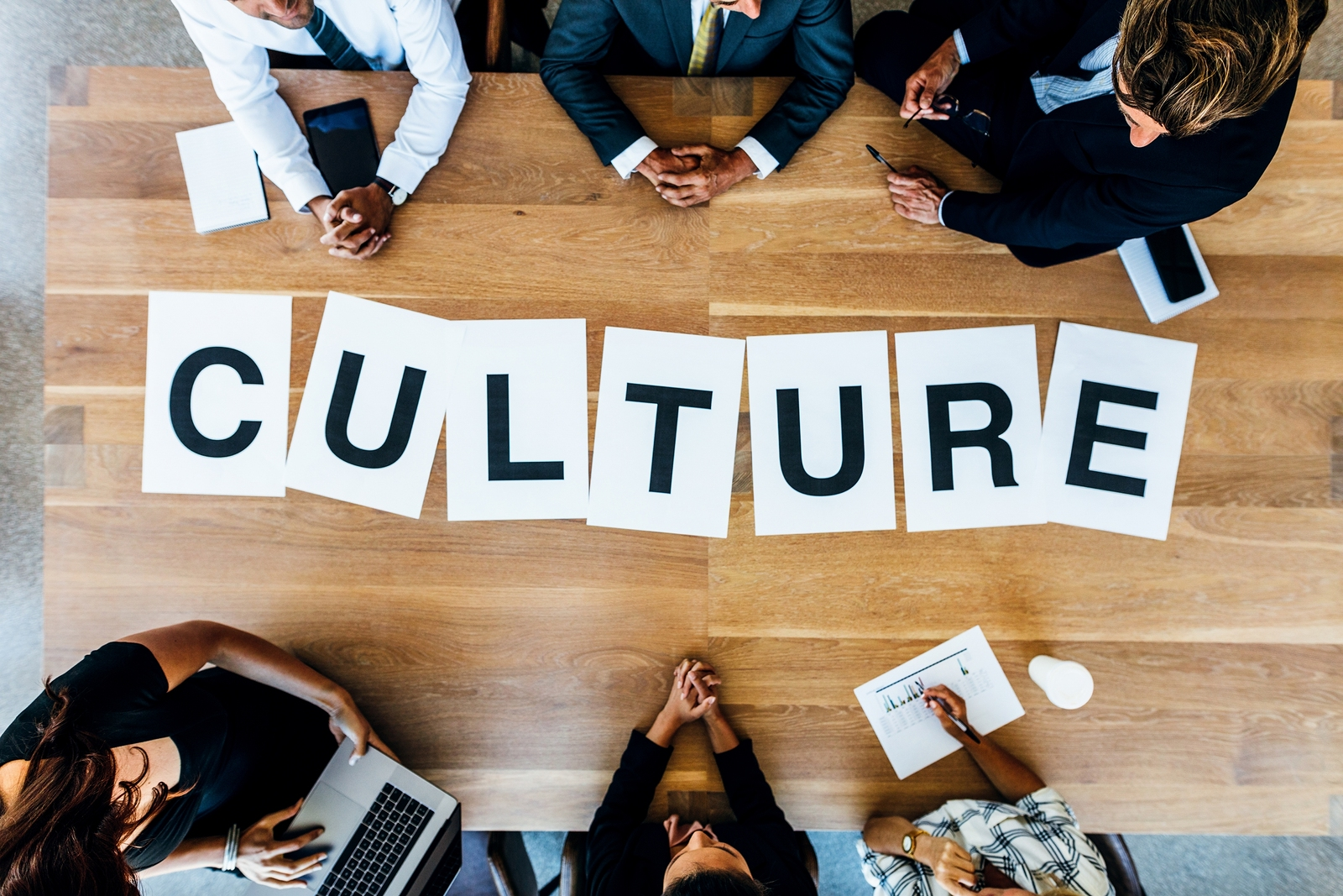 """A group of colleagues sitting at a conference table with the word """"culture"""" written on it."""