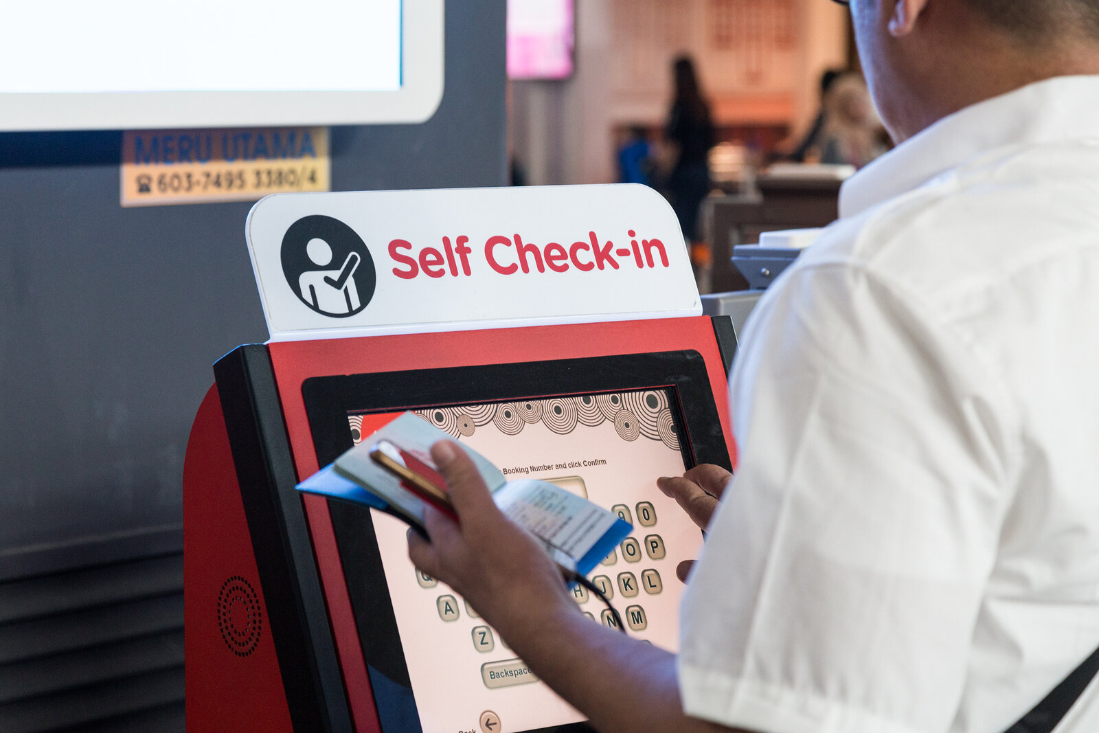A passenger using a self check-in kiosk at an airport.