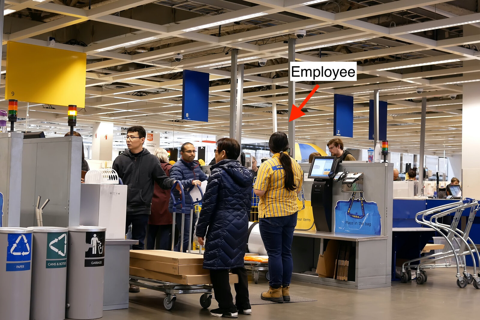 An Ikea employee stands ready to help customers in the self-checkout line.