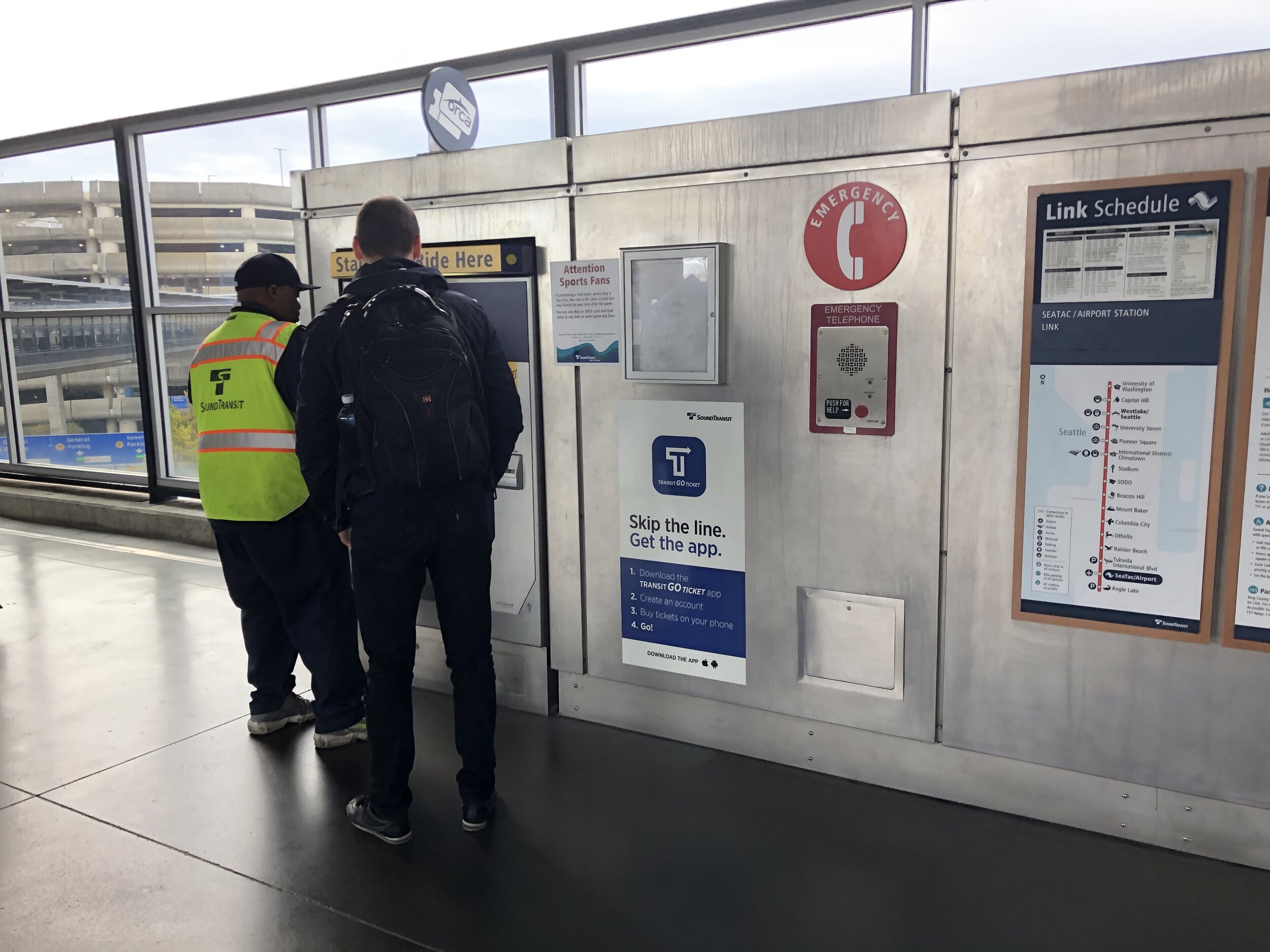 A light rail employee helping a passenger pay for their fare.