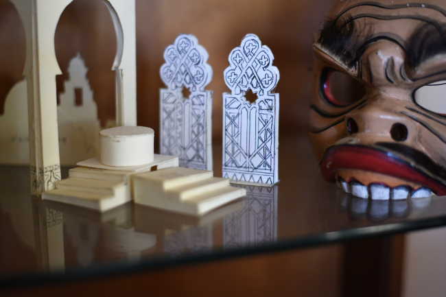 Miniature set designs intermingle with Candace's mask collection.