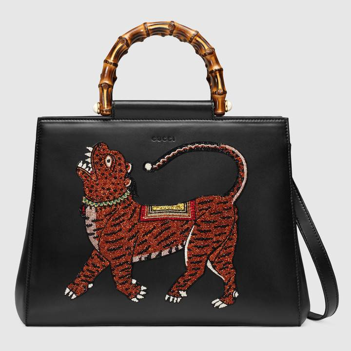 Turn heads with this iconic  Gucci Nymphaea  top handle bag, which is beautifully enhanced with a crystal embroidered tiger appliqué.