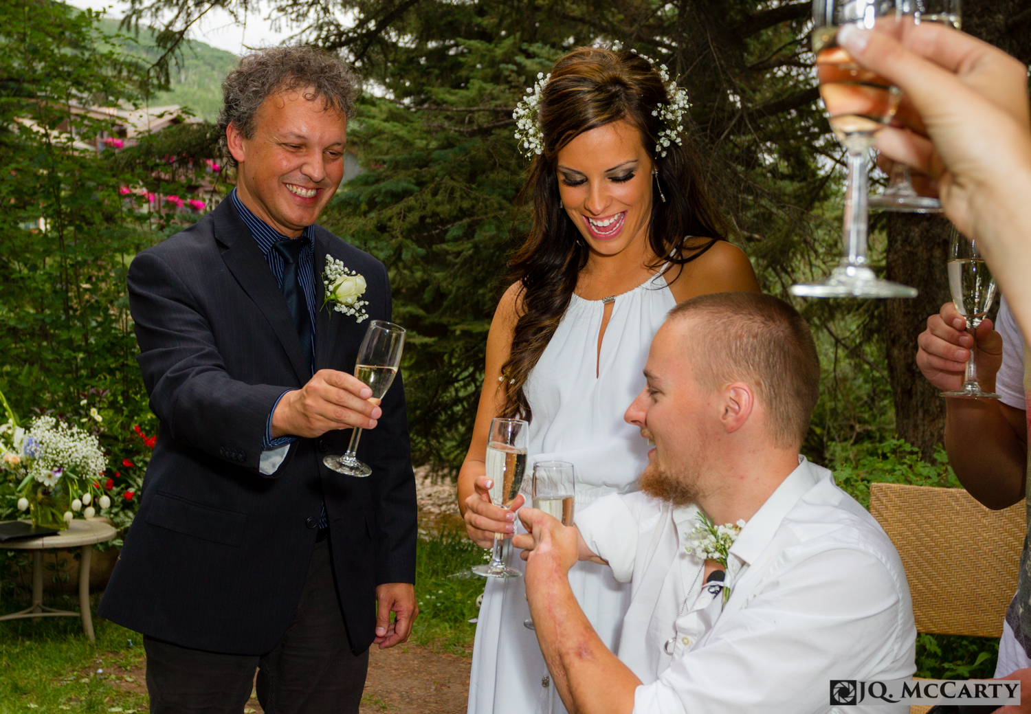 The father of the bride Michael MacVean, left, gives cheers to the newlywed couple after making a toast to his son-in-law's couragous path in courting his daughter after their impromptu wedding Wednesday at the Sonnenalp Hotel in Vail.