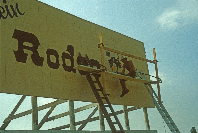Rick Stevens working on a highway billboard