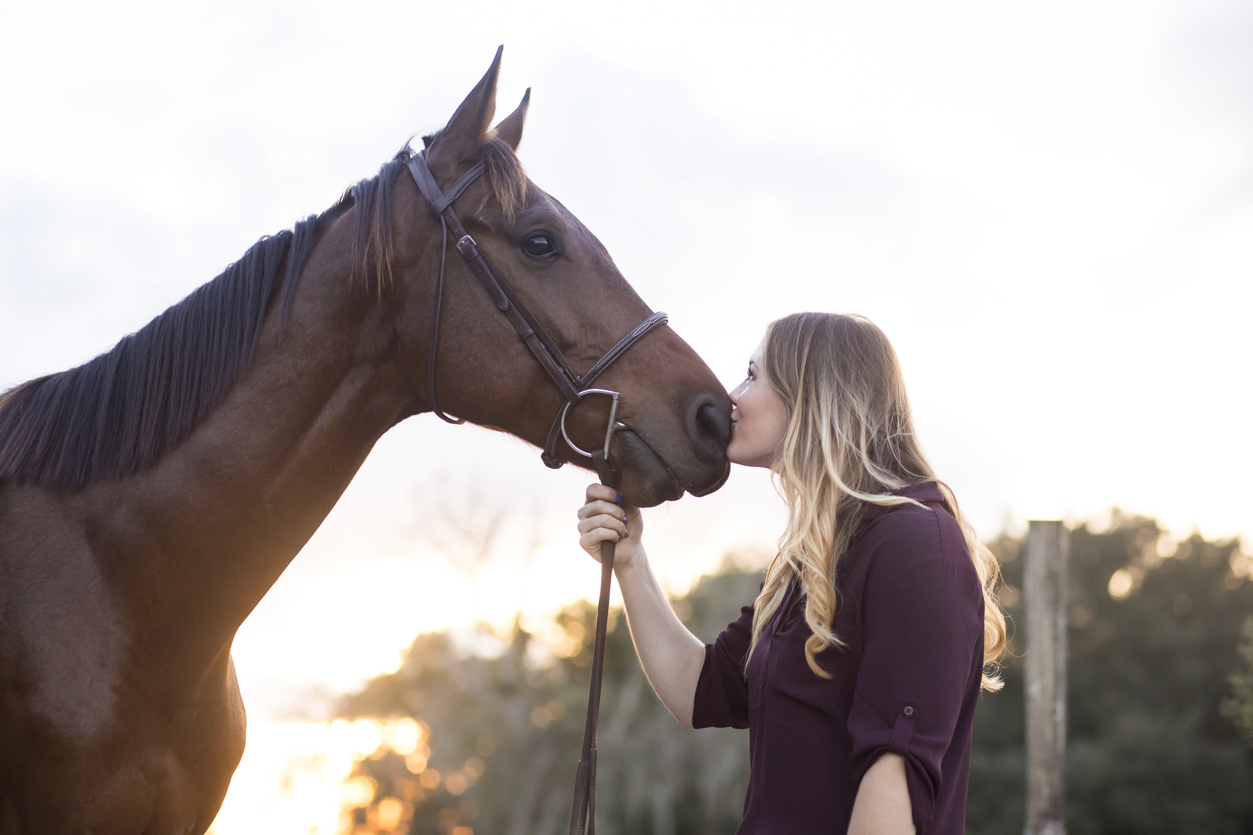 Young girl gives horse a kiss
