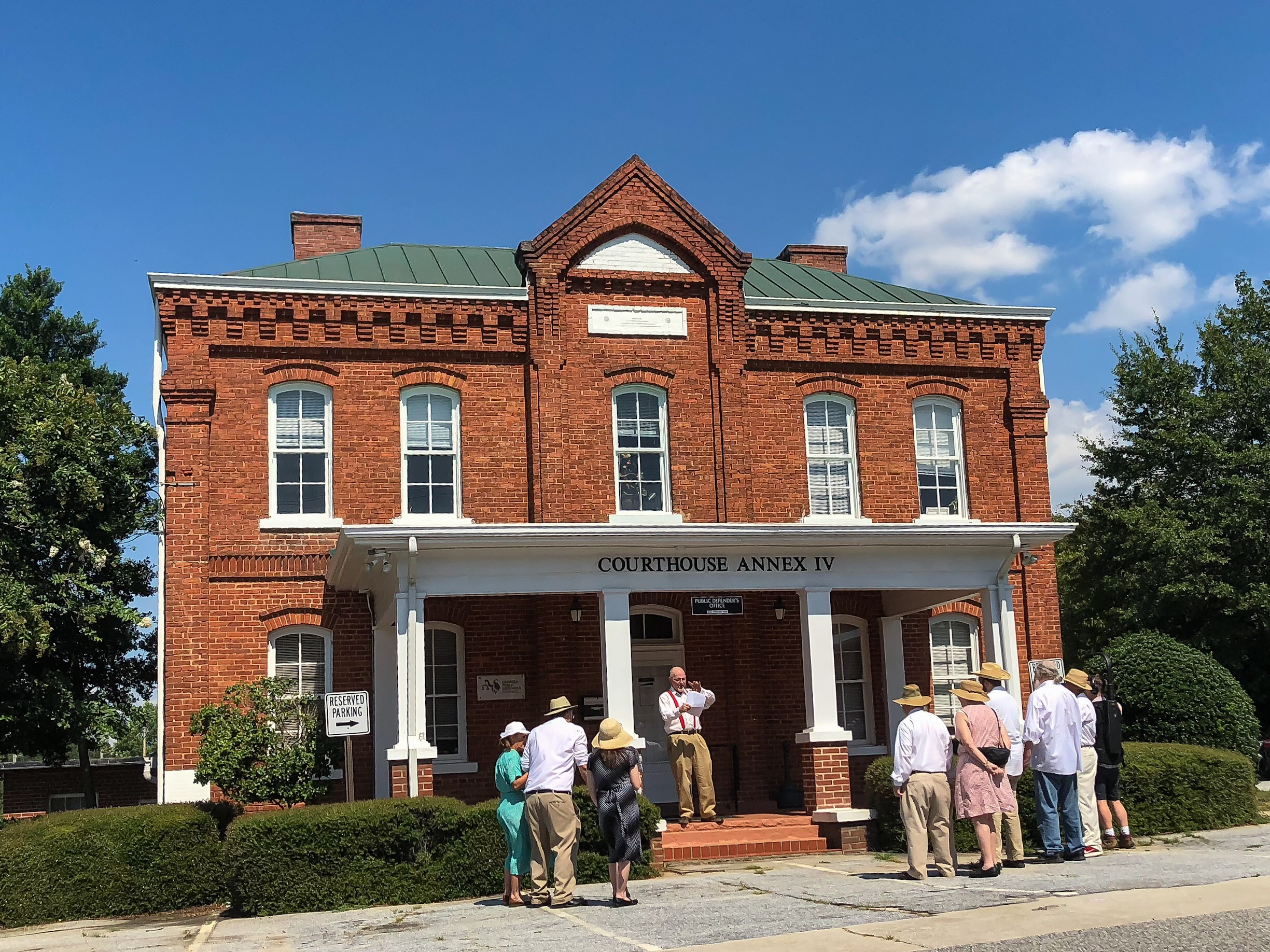 Attendees of the Moore's Ford Re-enactment gather outside the building that was the original jail in Monroe, GA. This jail is the location where Roger Malcom was held and released to Loy Harrison prior to meeting his death at the Moore's Ford Bridge.