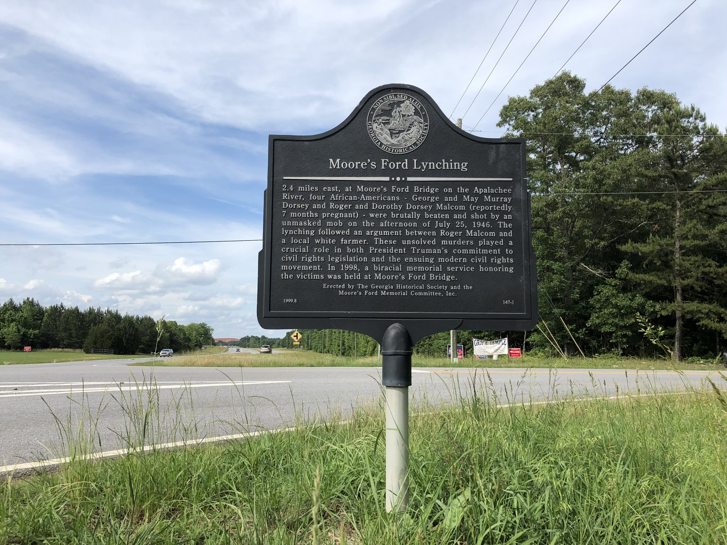 Historical marker on Highway 78 identifying the location of where to turn off the highway to reach the Moore's Ford Lynching site. The site, a bridge on the edge of Walton and Oconee counties, is several miles from this location in a rural setting.