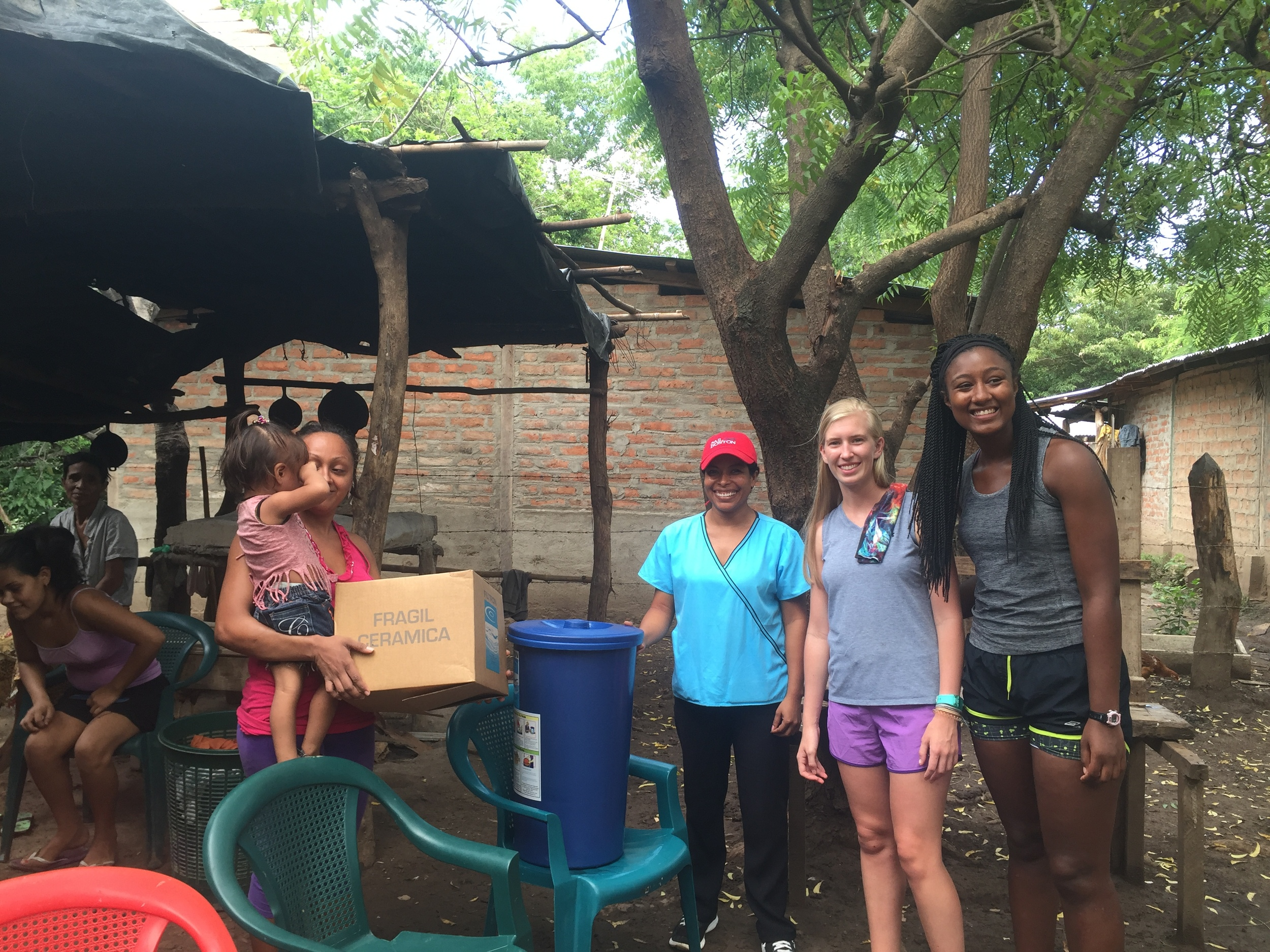 Fellows Reaves Houston and Sophia McFarlane distribute water filters to families that participate in Project Limón's Nutrition Program.