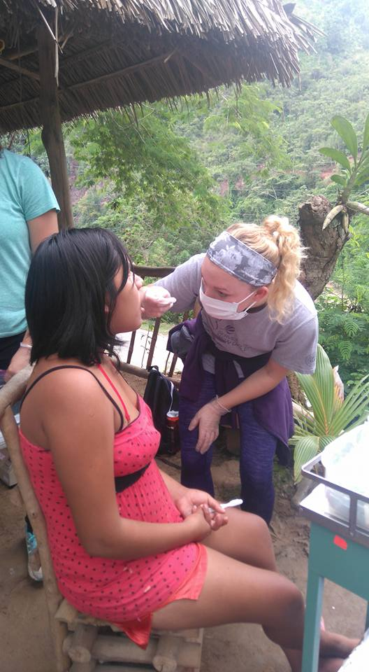 Ashley, one of our volunteers, gives fluoride to one of the community members.