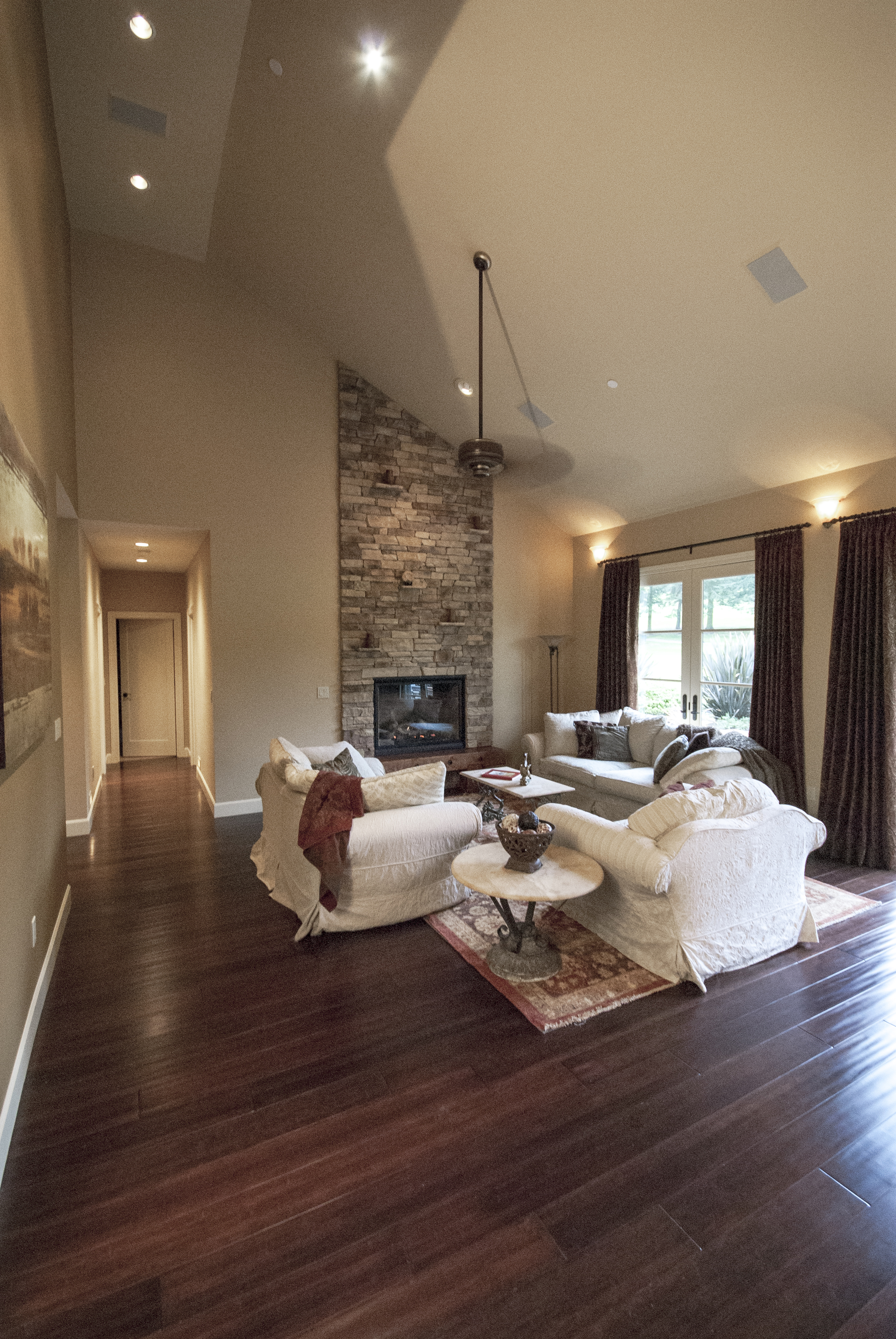 The great room concept is beautifully executed and includes a custom field stone floor to ceiling fireplace and vaulted ceilings.