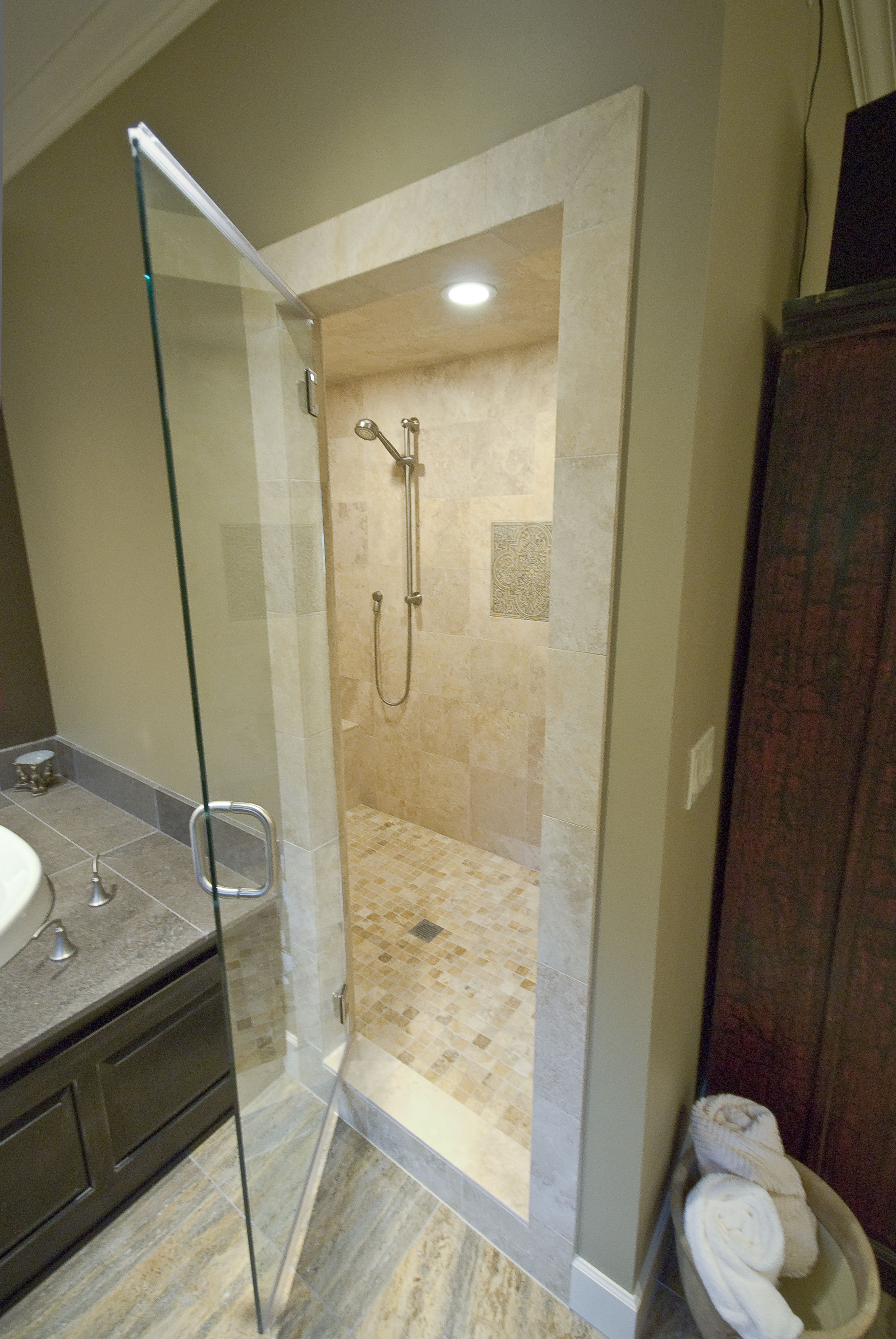 The steam shower was a must for him a sealed room with travertine tile floor to ceiling.  The tile is heated even in the shower and on the bench!