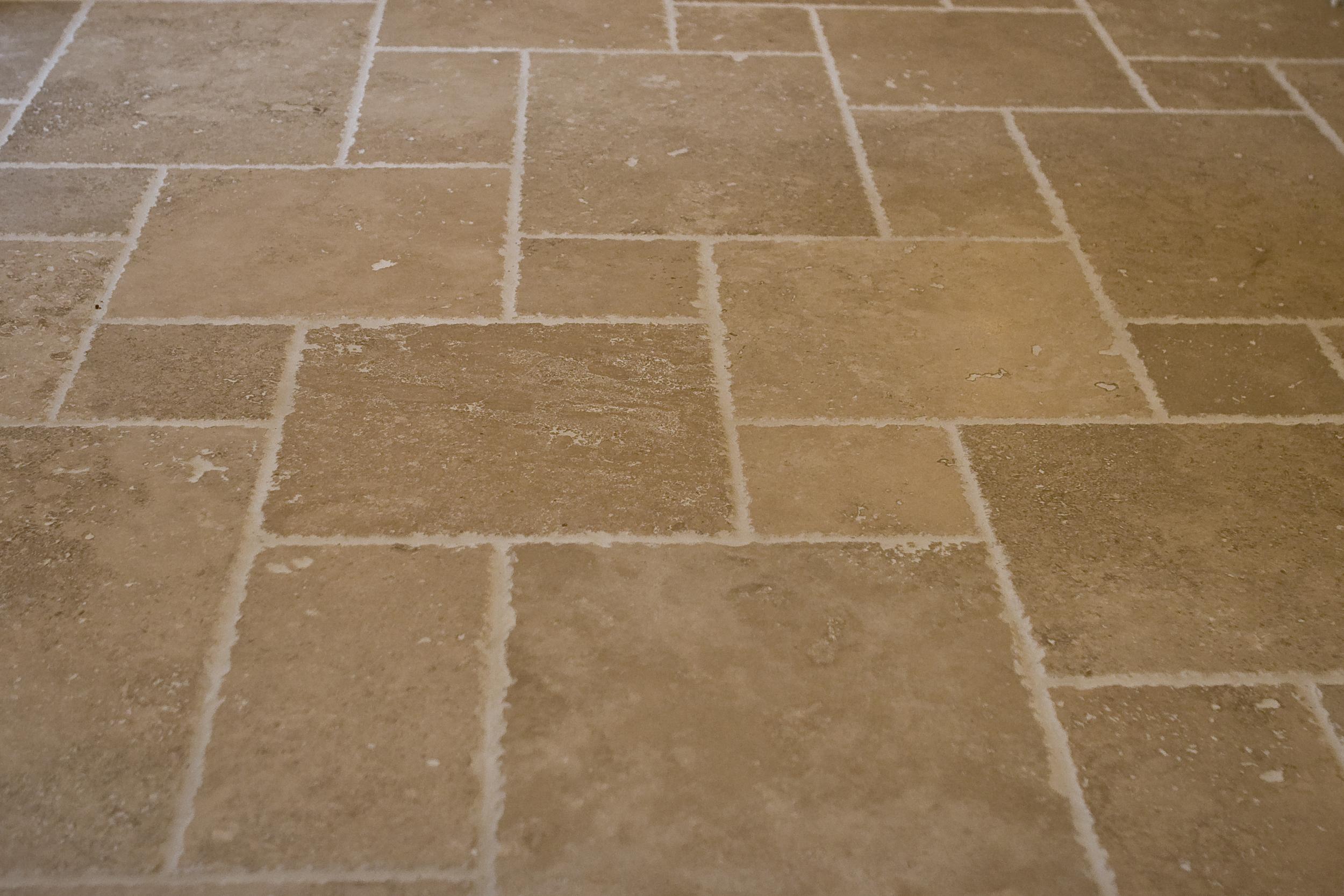"""Travertine tile laid in a """"pinwheel"""" pattern."""