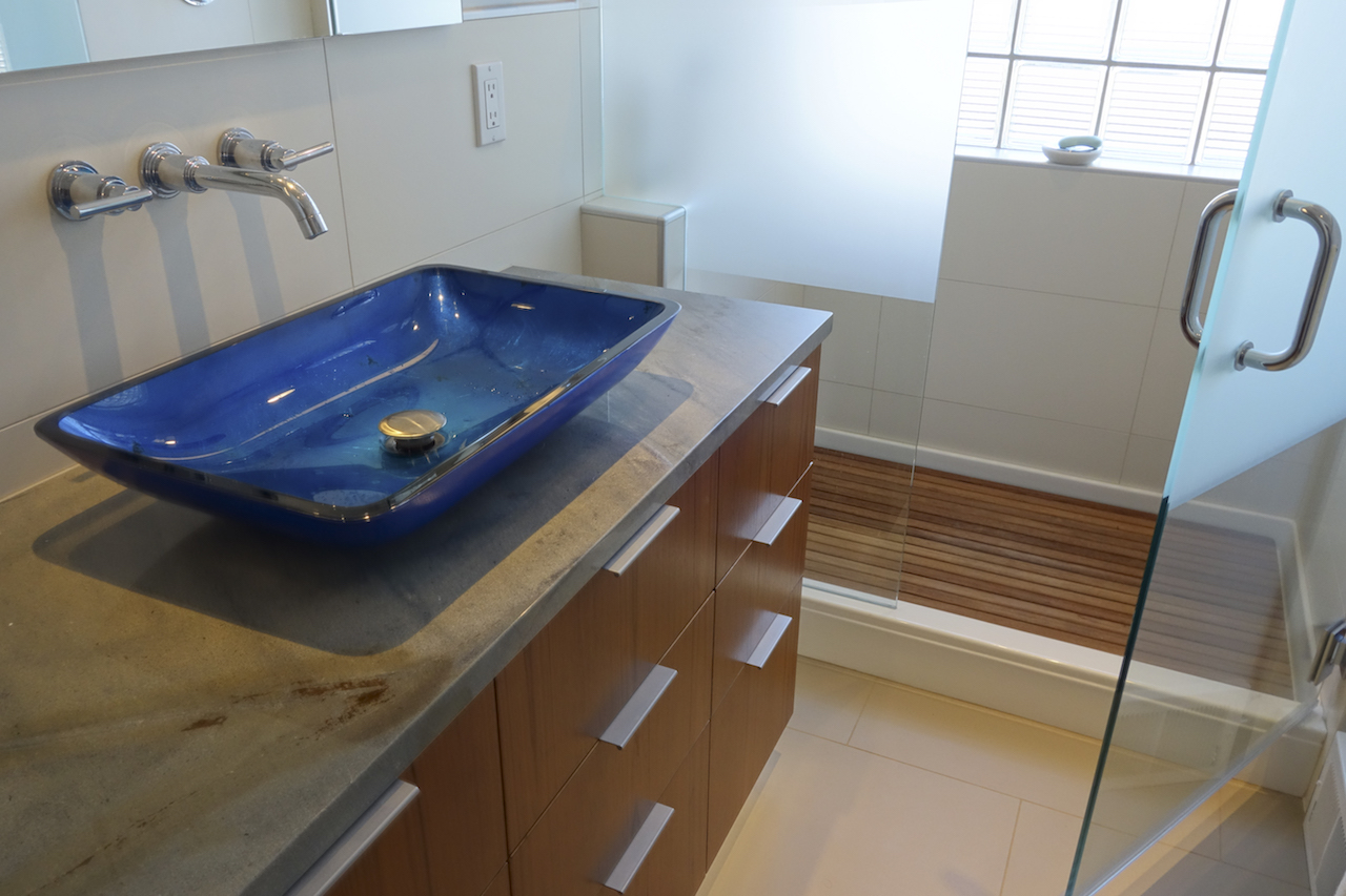 master bath with blue sink and wall mount faucet