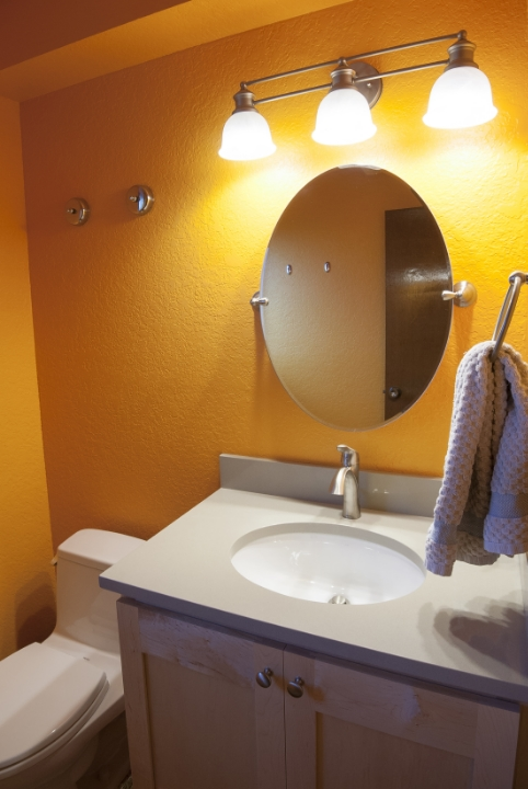 """This is an example of a simple inexpensive bathroom """"face lift"""". A new cabinet, solid surface countertop, under-mount sink, faucet, light fixture and toilet along with a bright paint scheme made the formerly dated and dreery powder bath warm and inviting."""