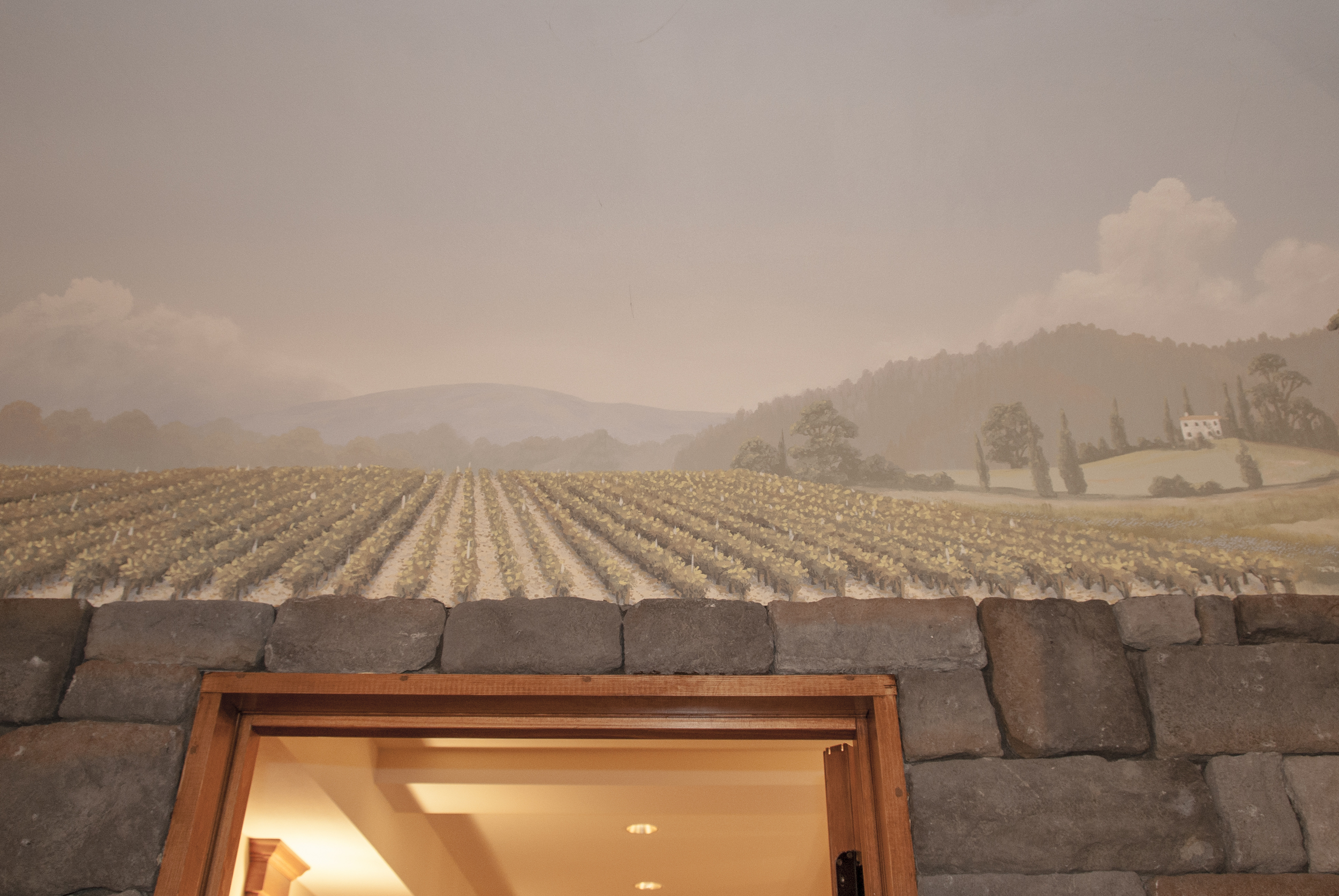 While he mural draws you in with stunning images of a Tuscan vineyard and countryside.