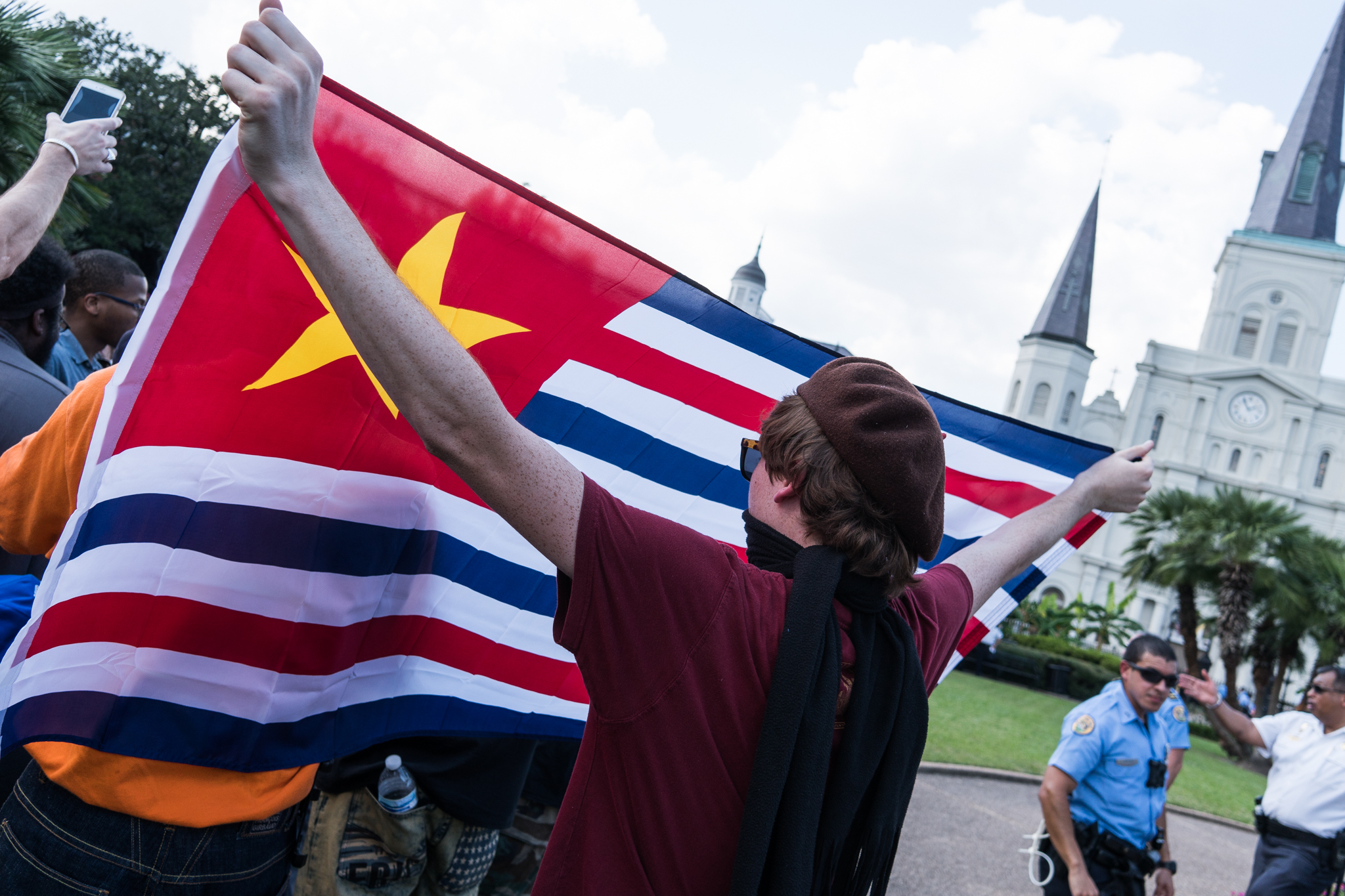 A protester holding a flag in Jackson Square.