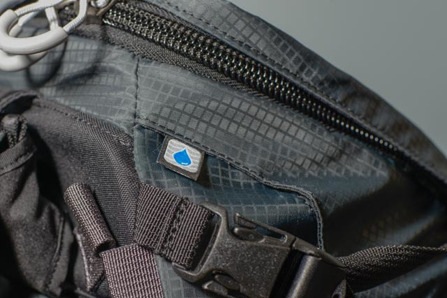 The exit point for the straw from the hydration pocket (bladder not included, but cheap to buy from REI). Notice the big zippers that are less likely to jam up with a little dirt or mud.