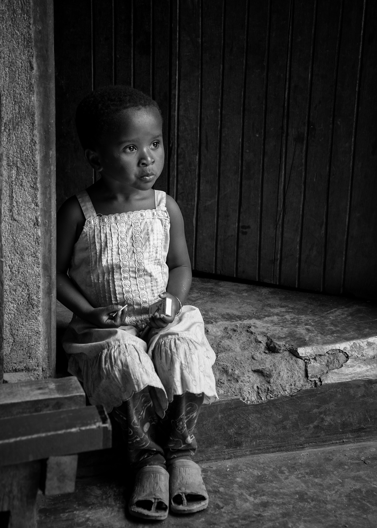 The daughter of a coffee farmer sits on the mud step outside her hut