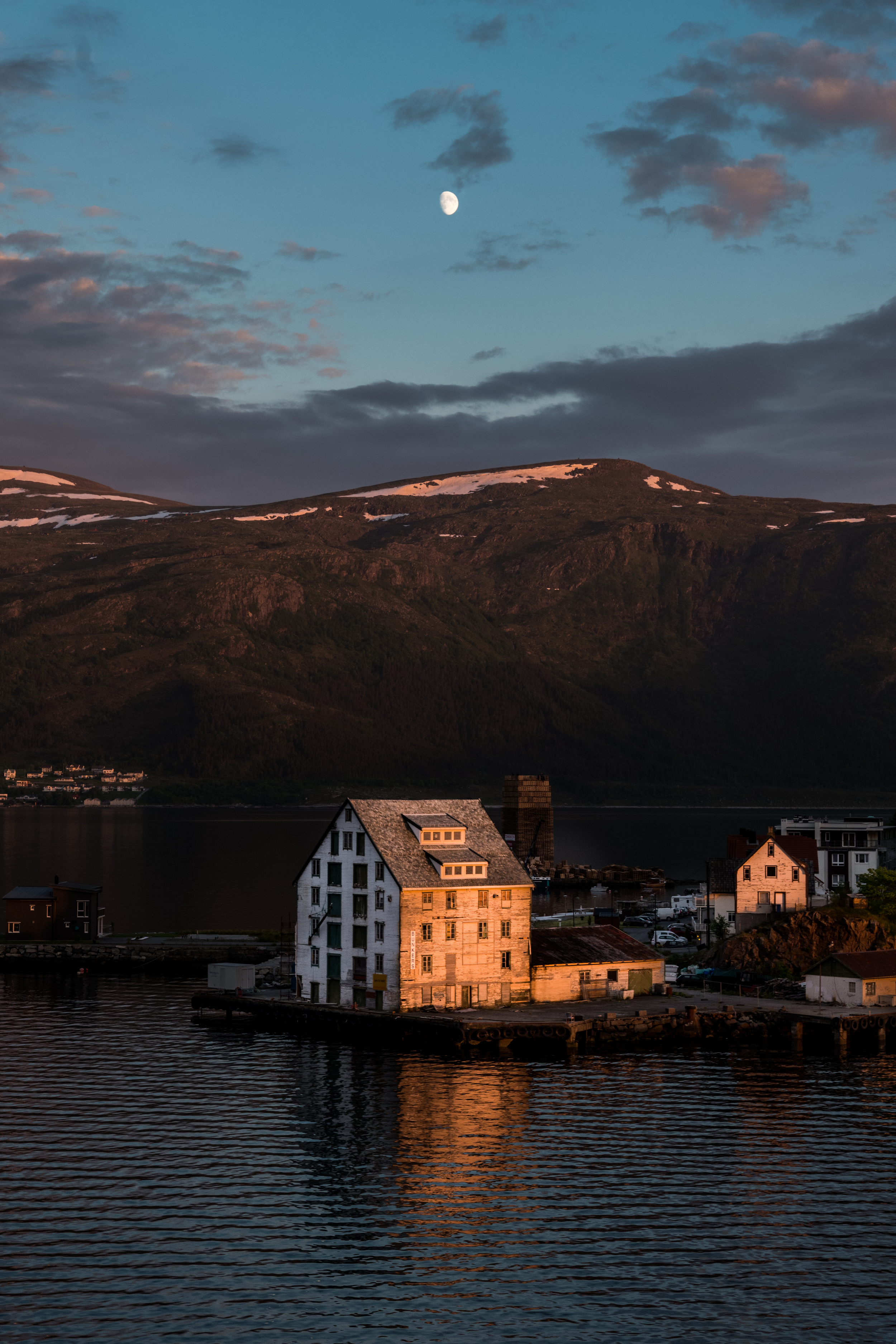 """Moonrise over Alesund, Norway - this was taken around midnight, showing the effect of the """"midnight sun"""" in the far north. The buildings in the foreground are fishing warehouses."""