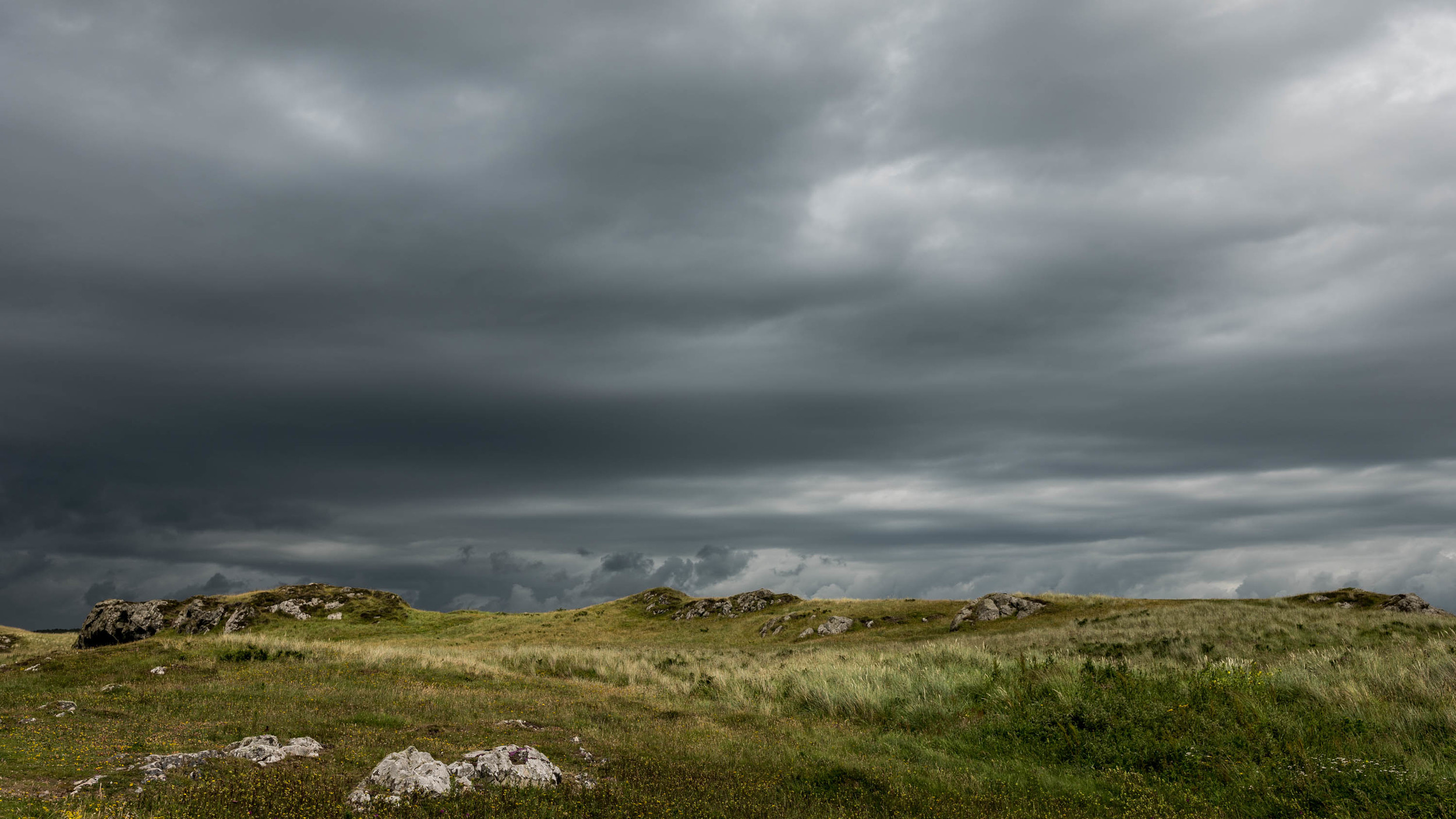 Dark storm clouds approach over Llanddwyn Island