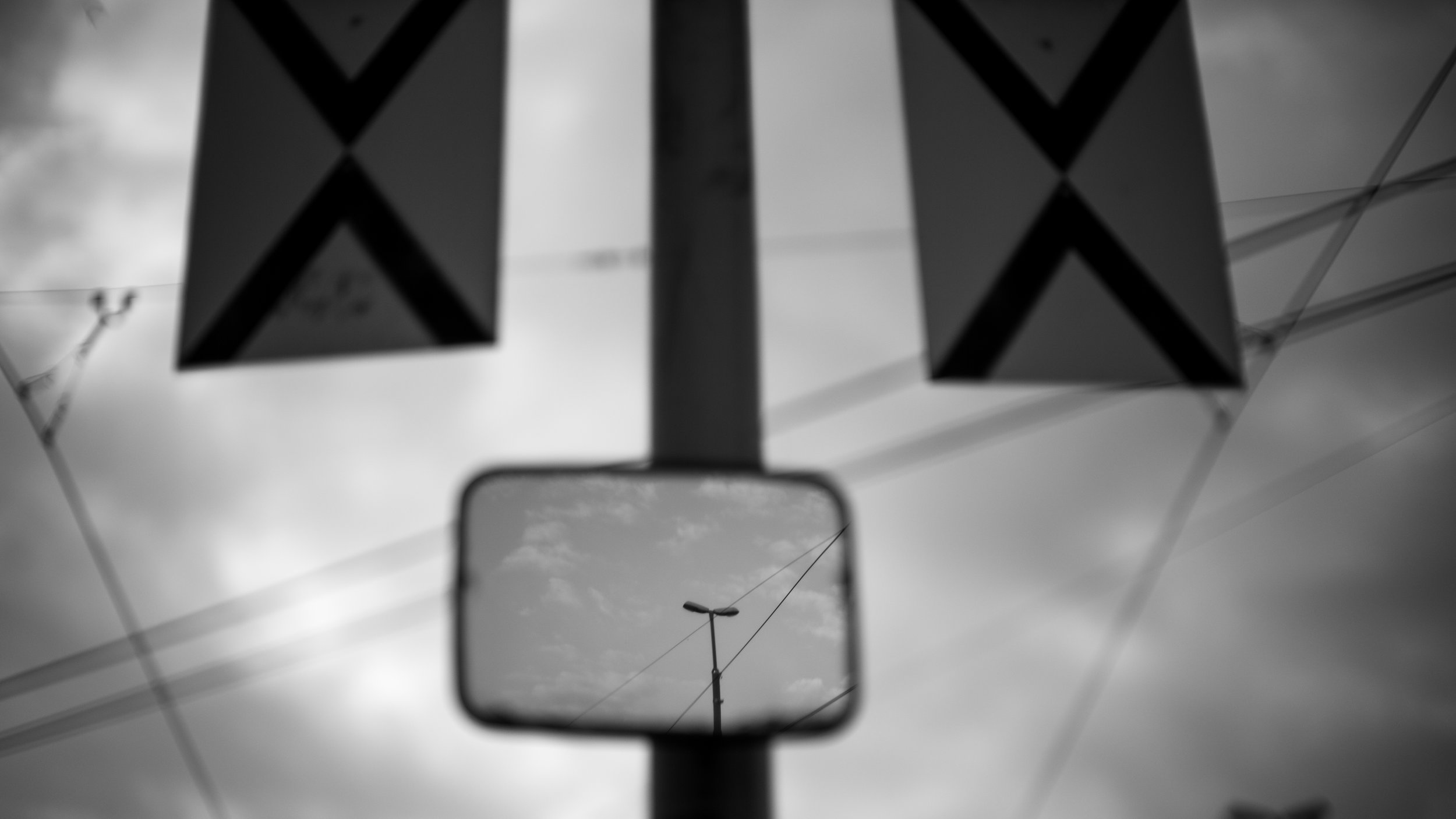 This is a bit of a surrealist image - a photograph of a light pole with a reflection of a light pole