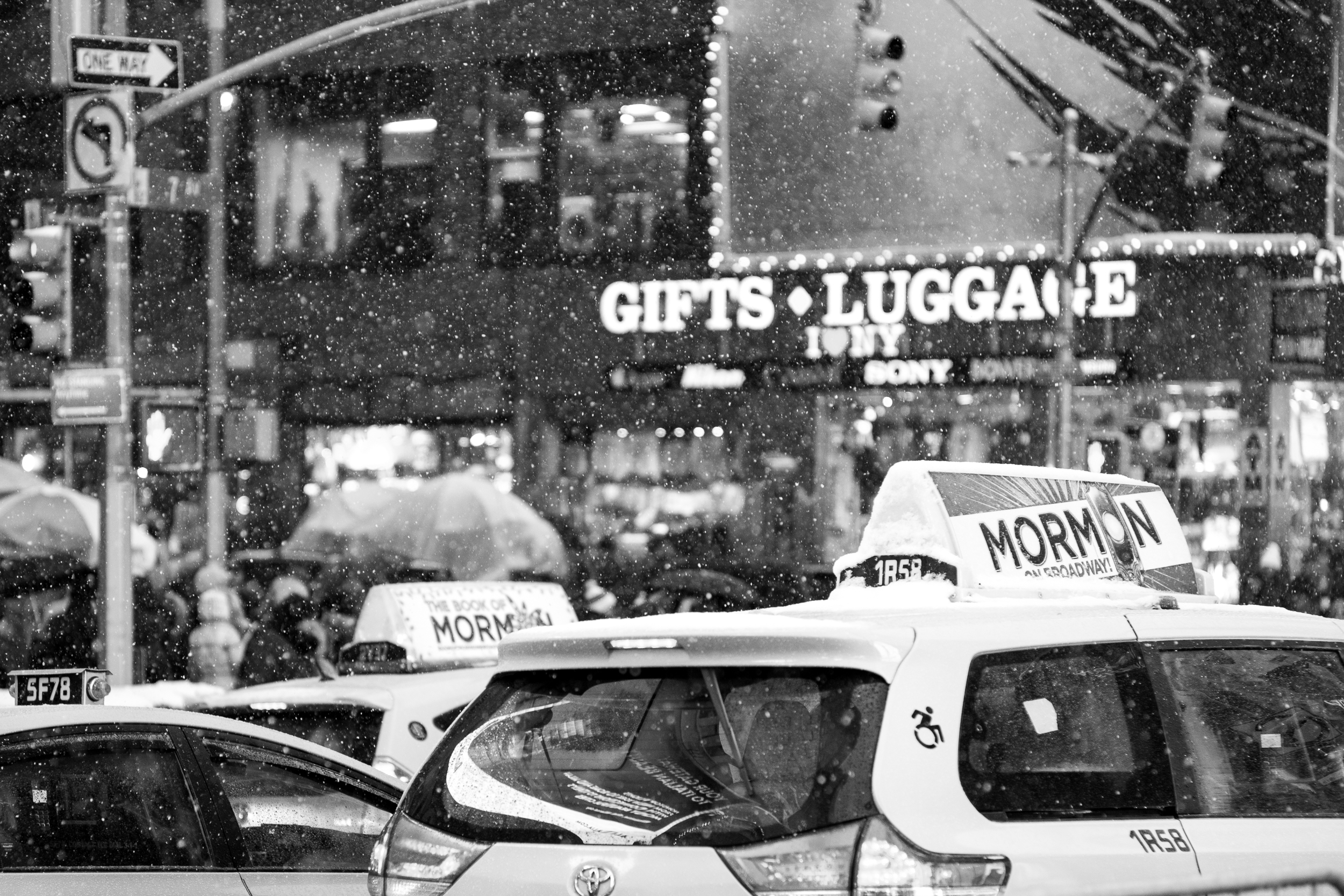 Taxi cabs lined up on the streets of Times Square during a late evening snowfall