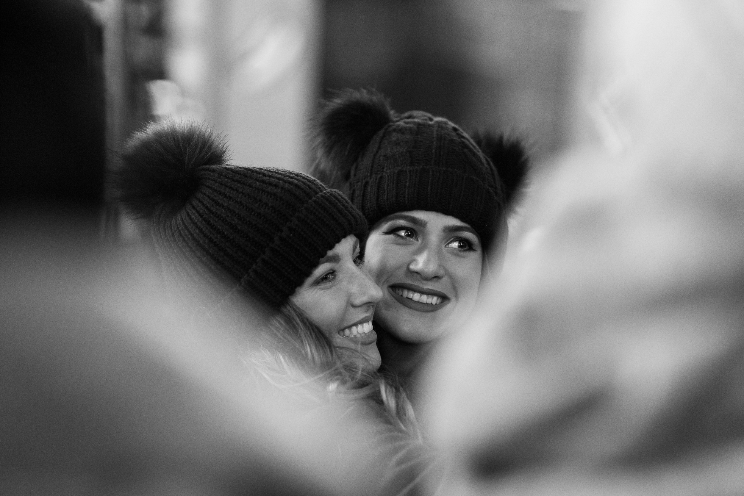 """BFFs. Two women pose for a photograph in Times Square. I """"plucked them out of a crowd"""" by using a longer focal length and narrow depth of field, thereby blurring the people around them and focusing the attention of the photograph solely on their faces. Leica M10 with 90mm Summicron f/2."""