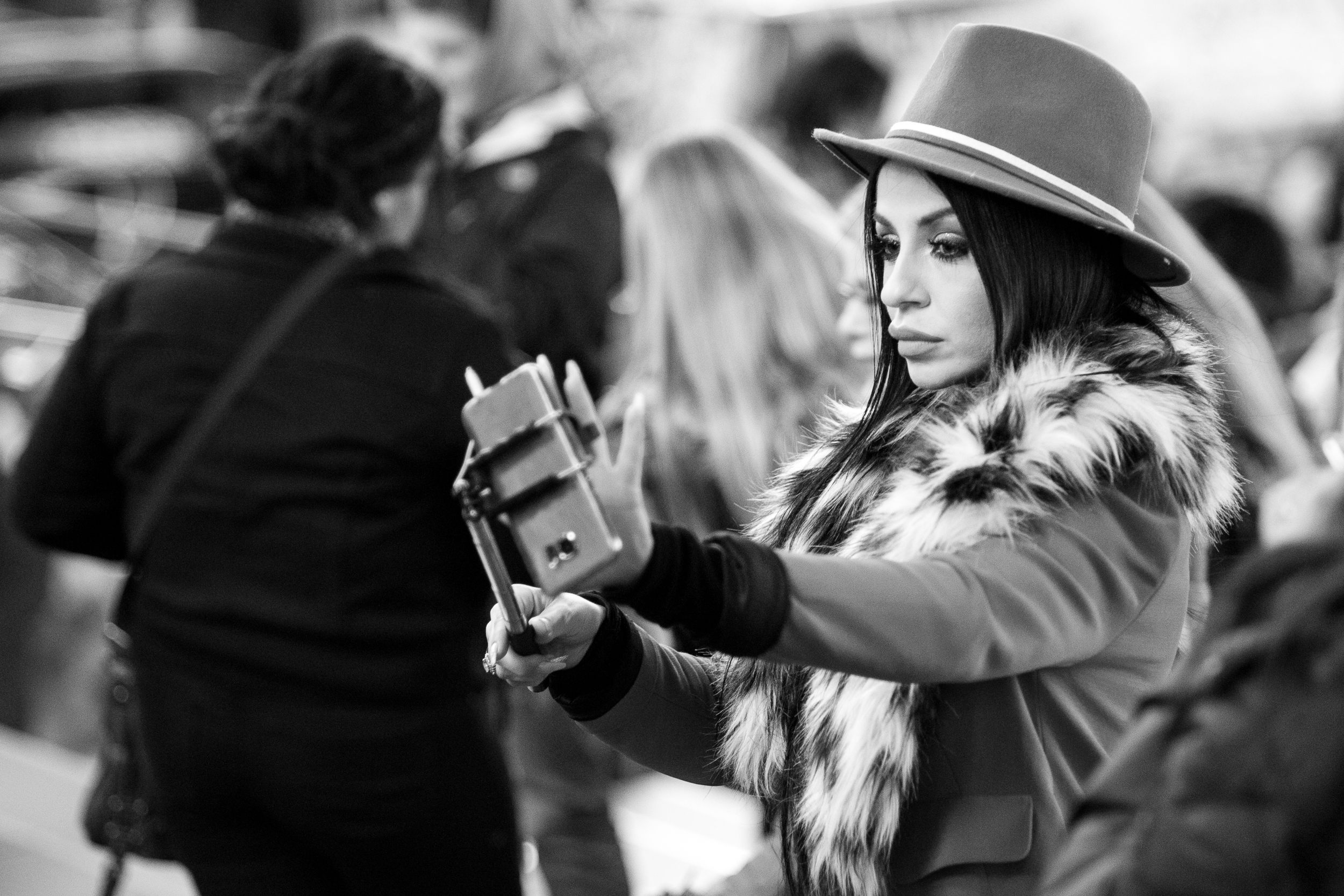 Selfie. A woman dressed up in her finest fashion prepares her selfie in Times Square. Leica M10 with 90mm Summicron f/2.