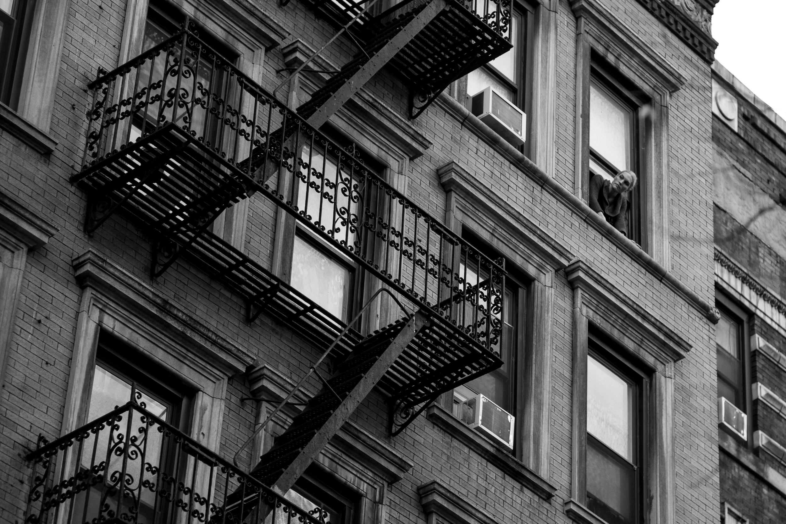 I spy. A woman looks out from her window on the busy New York streets below.Leica M10 with 90mm Summicron f/2.