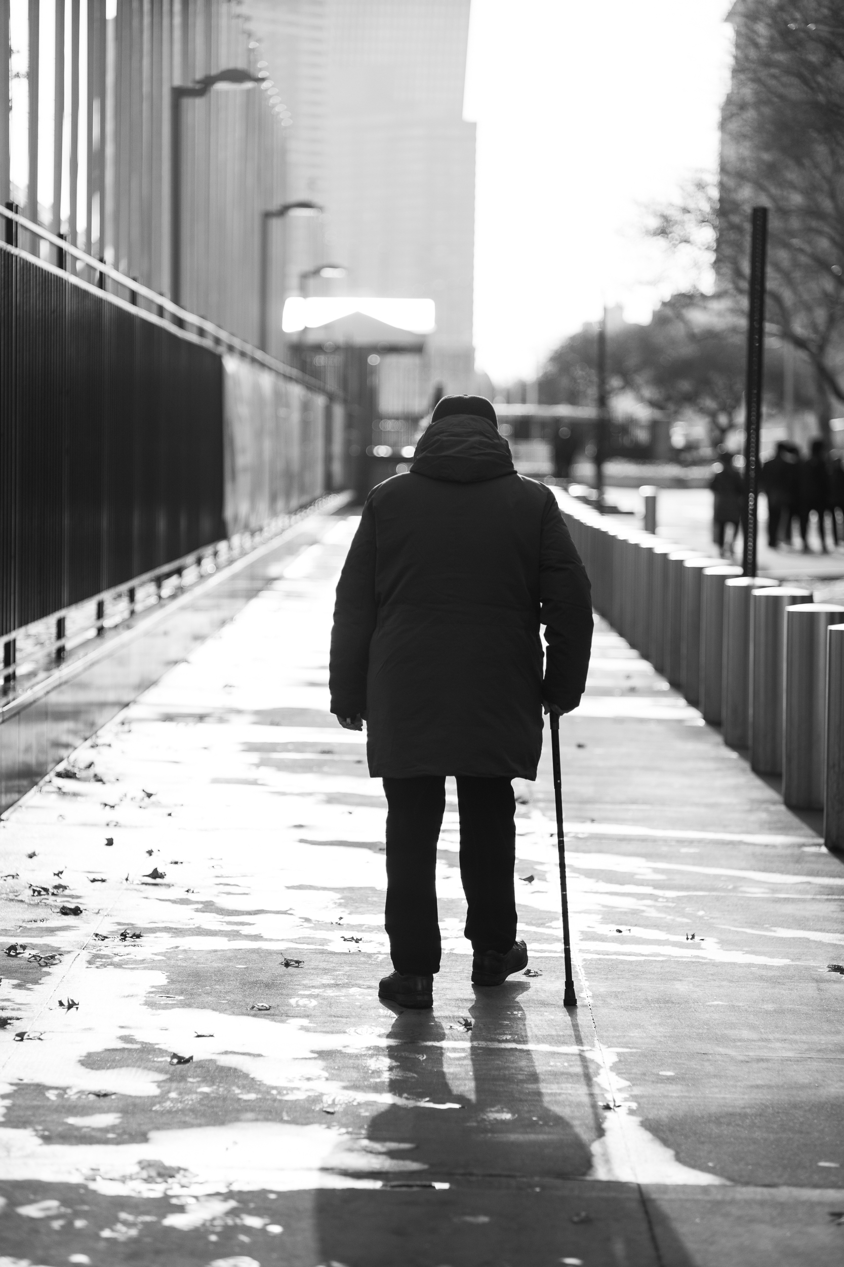 Stroll.  A man walks in front of the United Nations building. The harsh light and strong shadow became the sparkle that drew me to make this image.  Leica M10 with 35mm Summicron f/2.