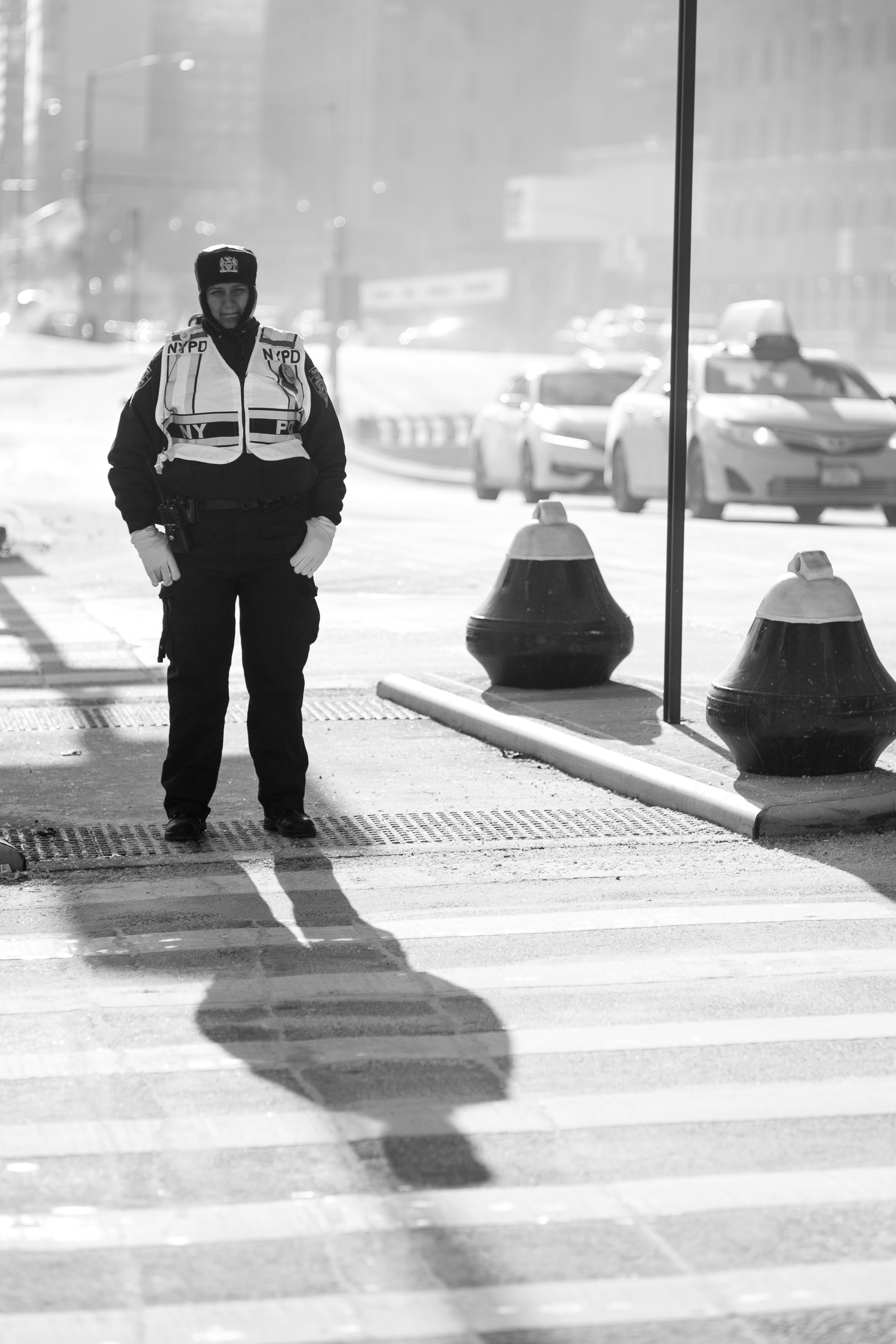 Patience. A police officer waits patiently for the light to chance before she begins directing more traffic over the intersection. The harsh light and strong shadows gave this scene the sparkle I was looking for. Leica M10 with 90mm Summicron f/2.