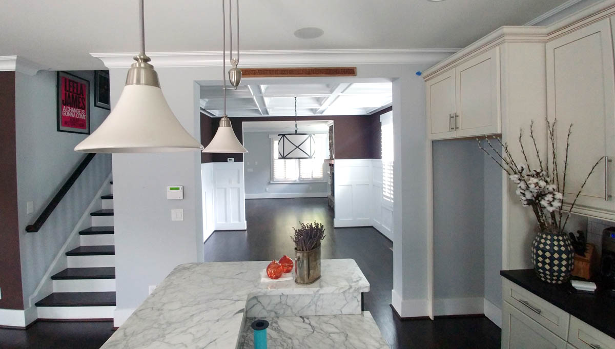 Stunning Kitchen renovation with marble, multi-height island, dark floors, and a fresh color palette for cabinets and walls.