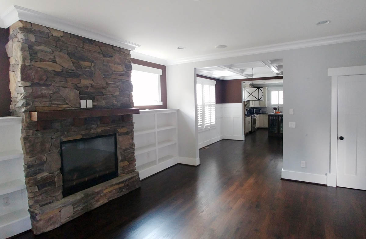 Adjacent family room is open to dining room and kitchen and includes a stone fireplace and built-in bookcases.