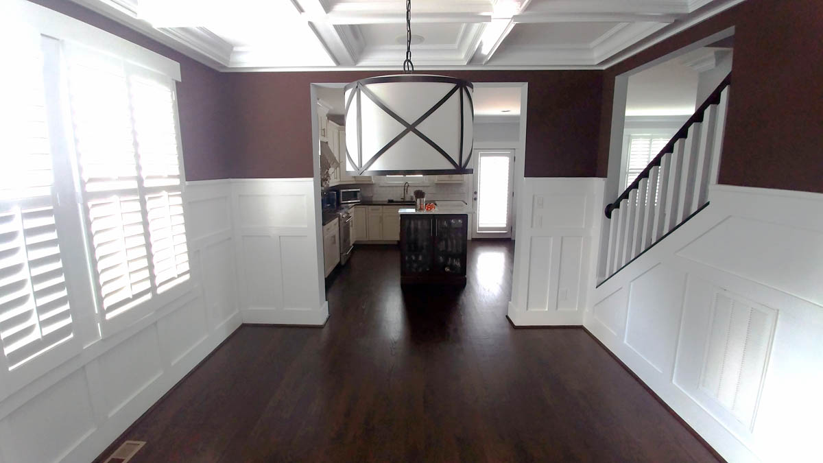 Dining room with detailed chair rail molding has wide opening to kitchen for easy-flow entertaining.