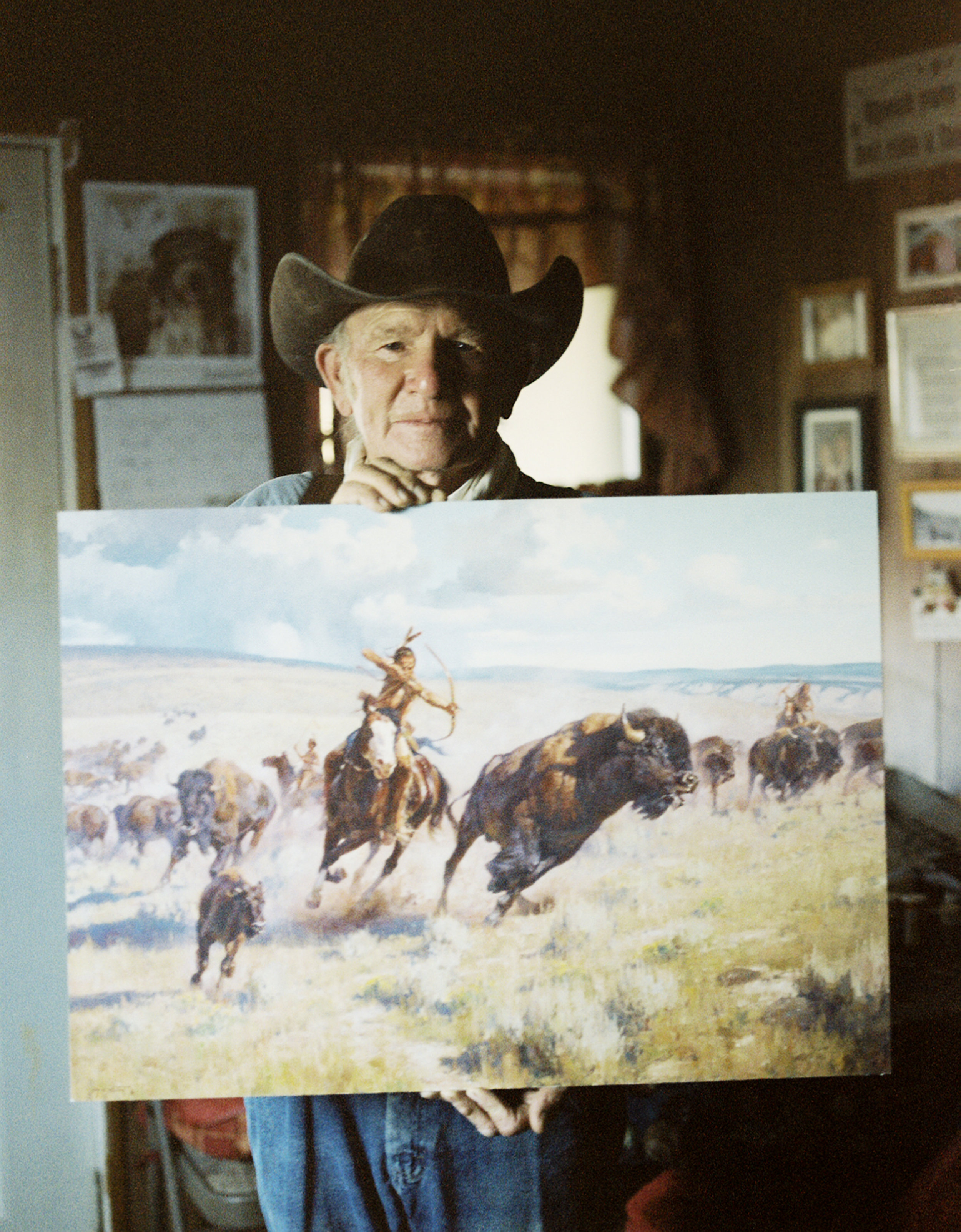 A rancher holding a painting of the wild west based on his horses. This painting won first place in the Utah State Fair many years prior. Elberta, population 256.